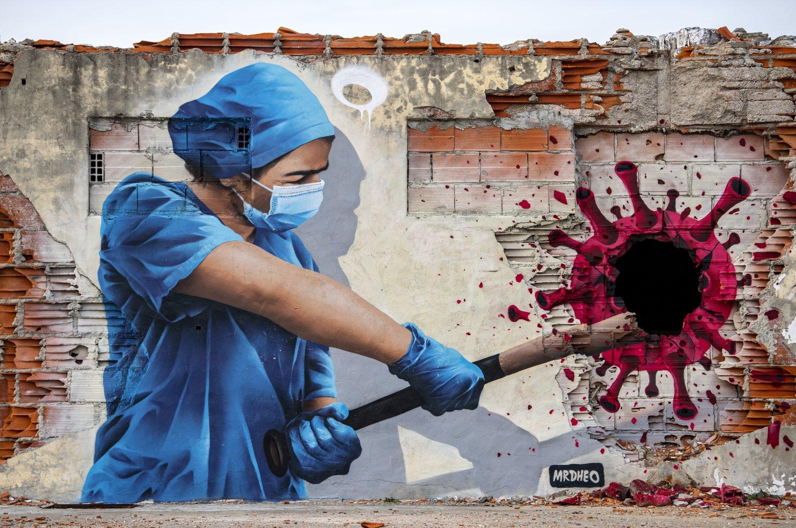 A street art mural depicts a health worker hitting a coronavirus molecule with a baseball bat, in Vila Nova de Gaia, Portugal, Feb. 24, 2021. (Photo by Getty Images)