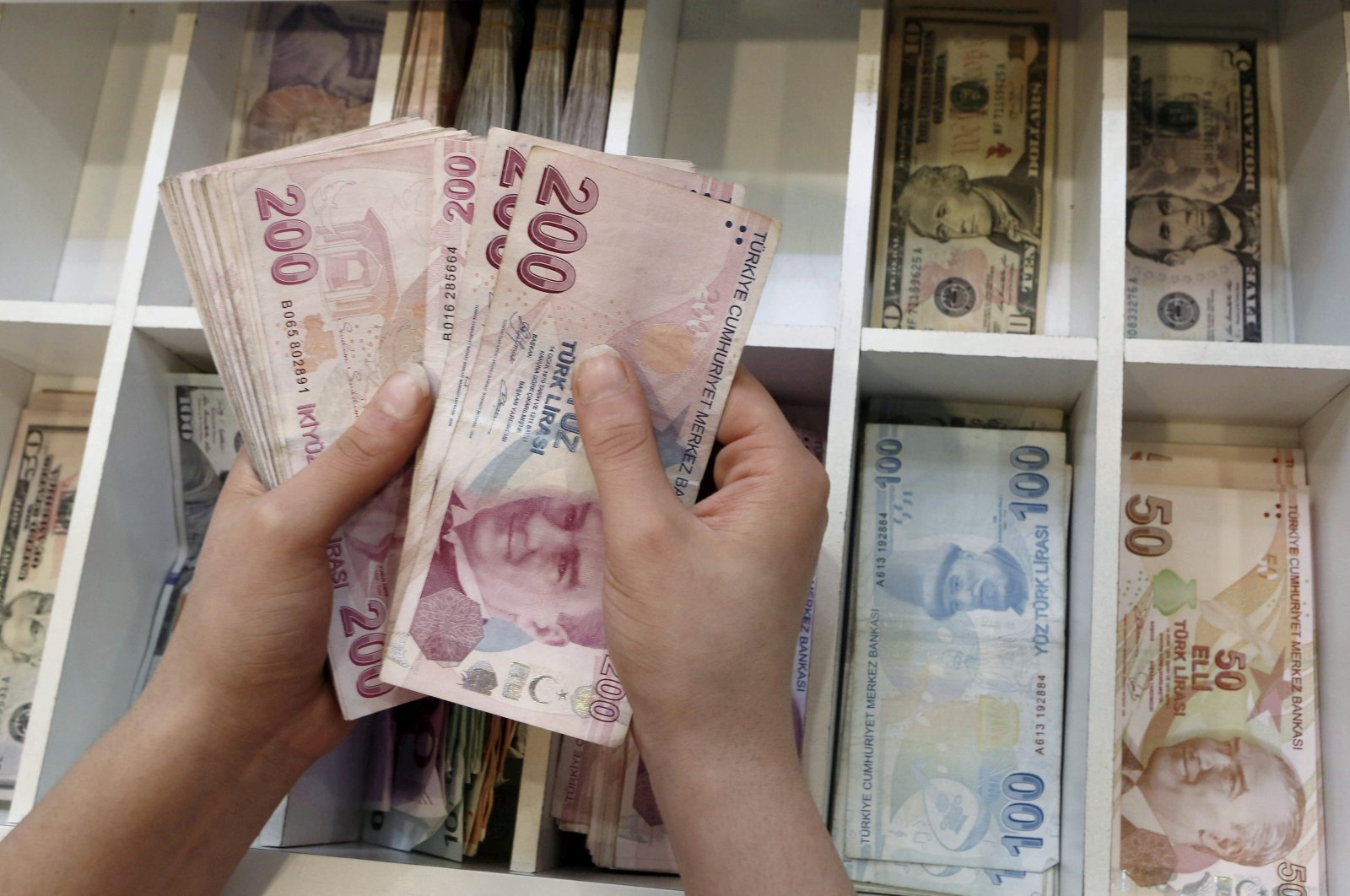 A money changer counts Turkish lira bills at a currency exchange office in central Istanbul, Turkey, Aug. 21, 2015. (Reuters Photo)
