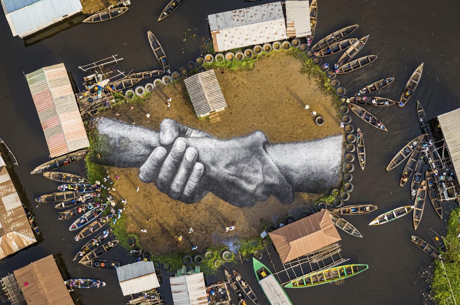An aerial view shows a giant land art fresco by French-Swiss artist Saype, painted for the 10th step of his worldwide 'Beyond Walls' project in Ganvie, village on stilts, Benin, Wednesday, March 3, 2021. (Valentin Flauraud for Saype via AP)