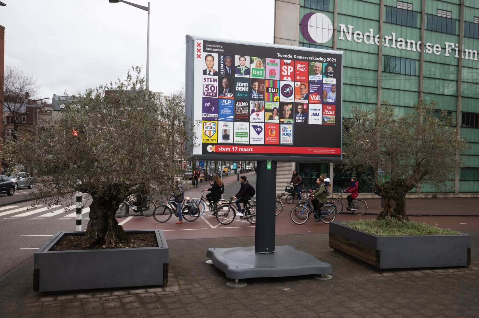 Cyclists at a road crossing near Dutch political party election campaign posters on a billboard in Amsterdam, Netherlands, on Tuesday, March 9, 2021. (Getty Images)