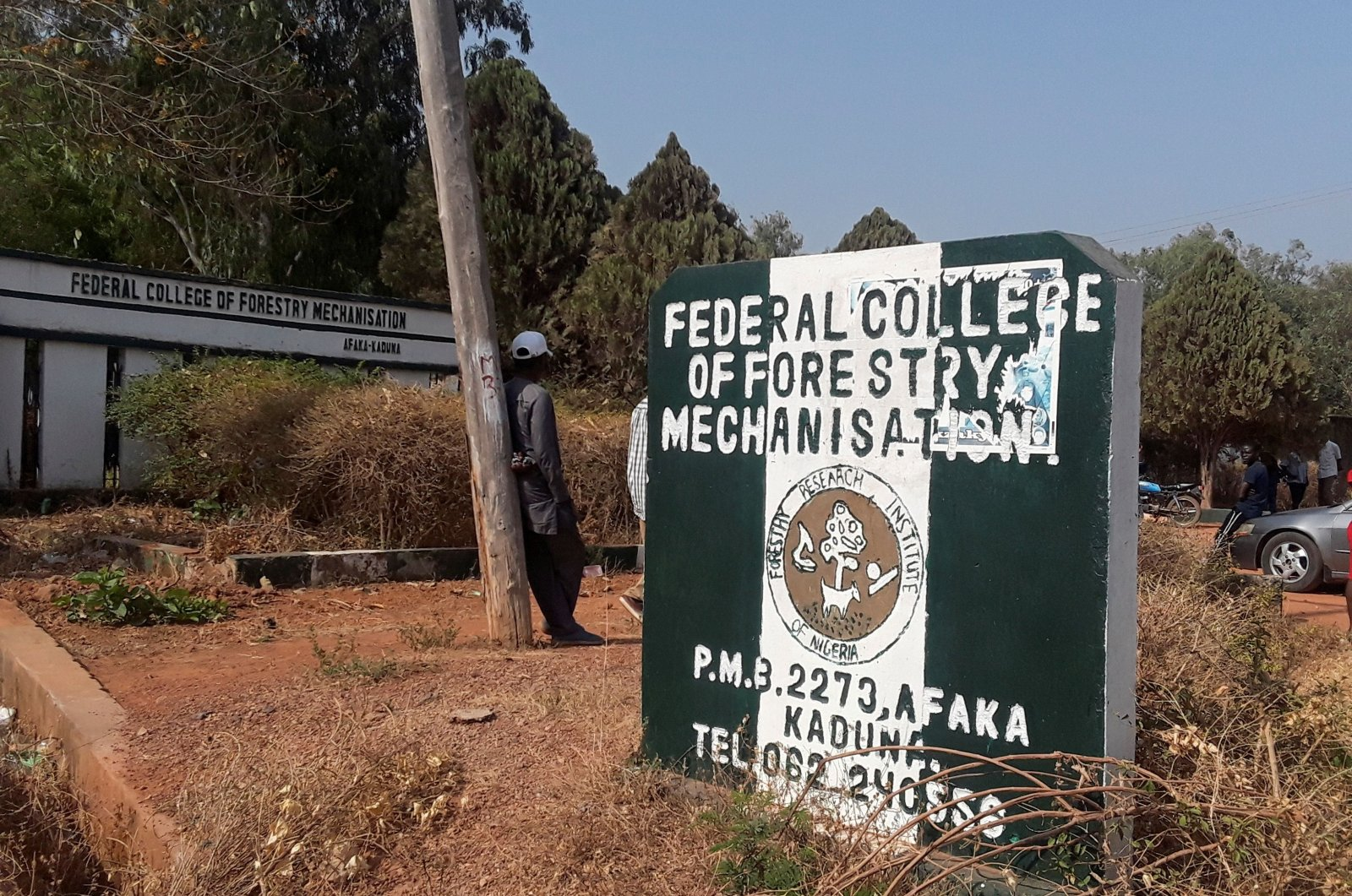 A man rests on a pole beside the signage of the Federal College of Forestry Mechanisation where gunmen abducted students, in Kaduna, Nigeria March 12, 2021. (Reuters Photo)