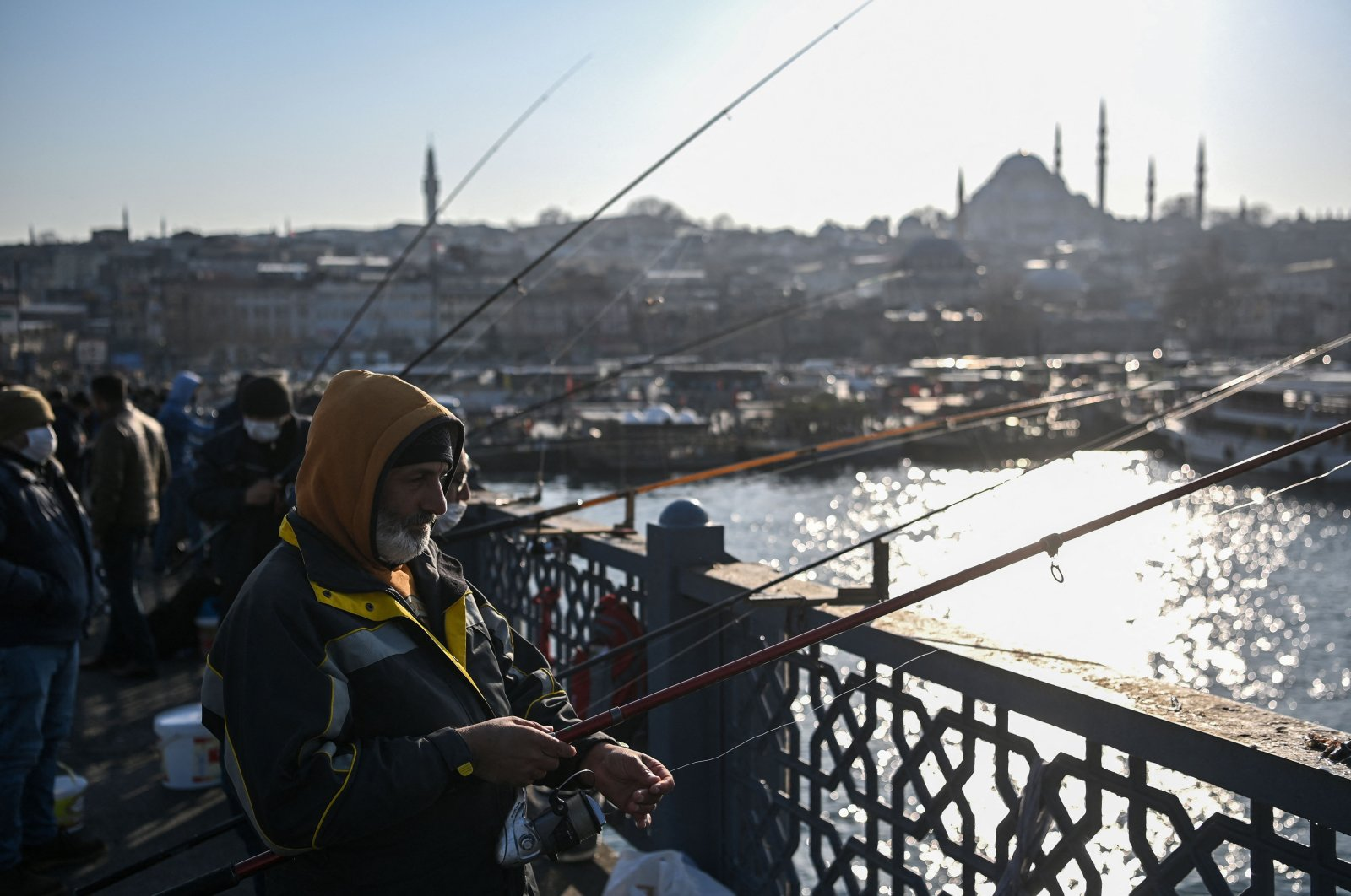 Men fish on the Galata Bridge with the Süleymaniye mosque in the background, in Istanbul's historic Eminönü district on March 9, 2021. (AFP Photo)