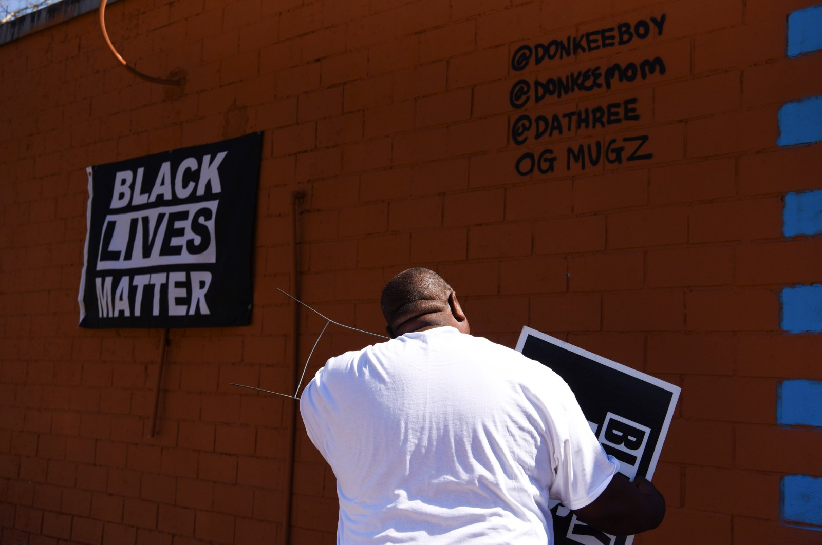 Travis Cains, who grew up in Cuney Homes with George Floyd, adjusts a Black Lives Matter sign in front of a mural of Floyd in the Third Ward ahead of the trial of the former Minneapolis cop Derek Chauvin in Houston, Texas, U.S., March 3, 2021. (Reuters Photo)