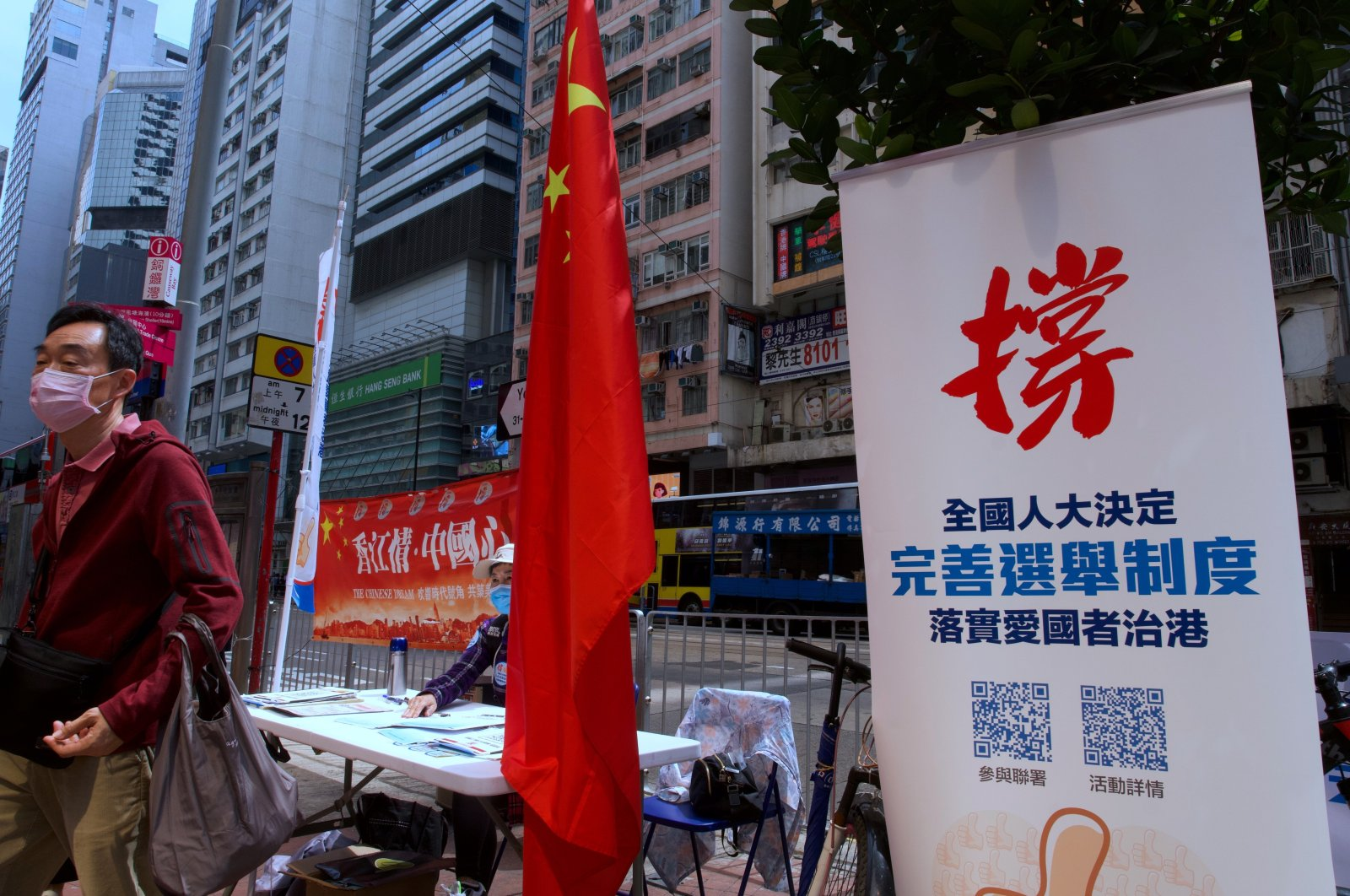 "A man walks past a banner that reads ""Support the proposal of National People's Congress (NPC) for the draft changes of election rules for Hong Kong"" at a downtown street in Hong Kong Thursday, March 11, 2021. (AP Photo)"