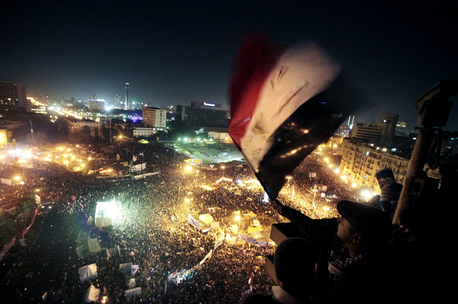 People wave flags in Tahrir Square to mark the first anniversary of the popular uprising that led to the quick ouster of autocrat President Hosni Mubarak, in Cairo, Egypt on Jan. 25, 2012 (AP File Photo)