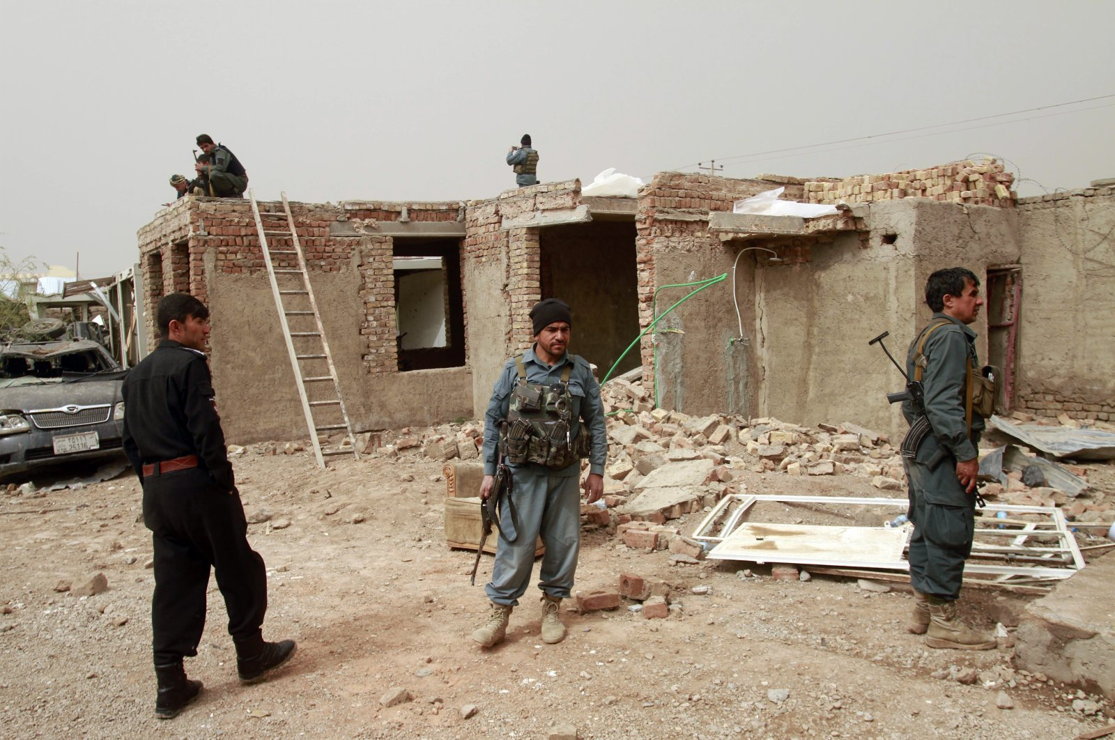 Security officials inspect the site of a car bomb attack in Herat province, west of Kabul, Afghanistan, Saturday, March 13, 2021. (AP Photo)
