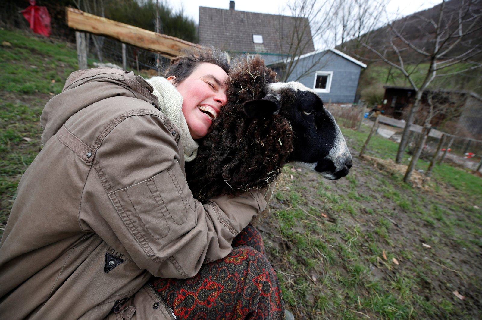 Lexa Voss, personality development coach, cuddles sheep Karlotta at her little farm, where she holds sheep cuddling seminars during COVID-19 lockdown in Hattingen, near Wuppertal, Germany, March 11, 2021. (Reuters)