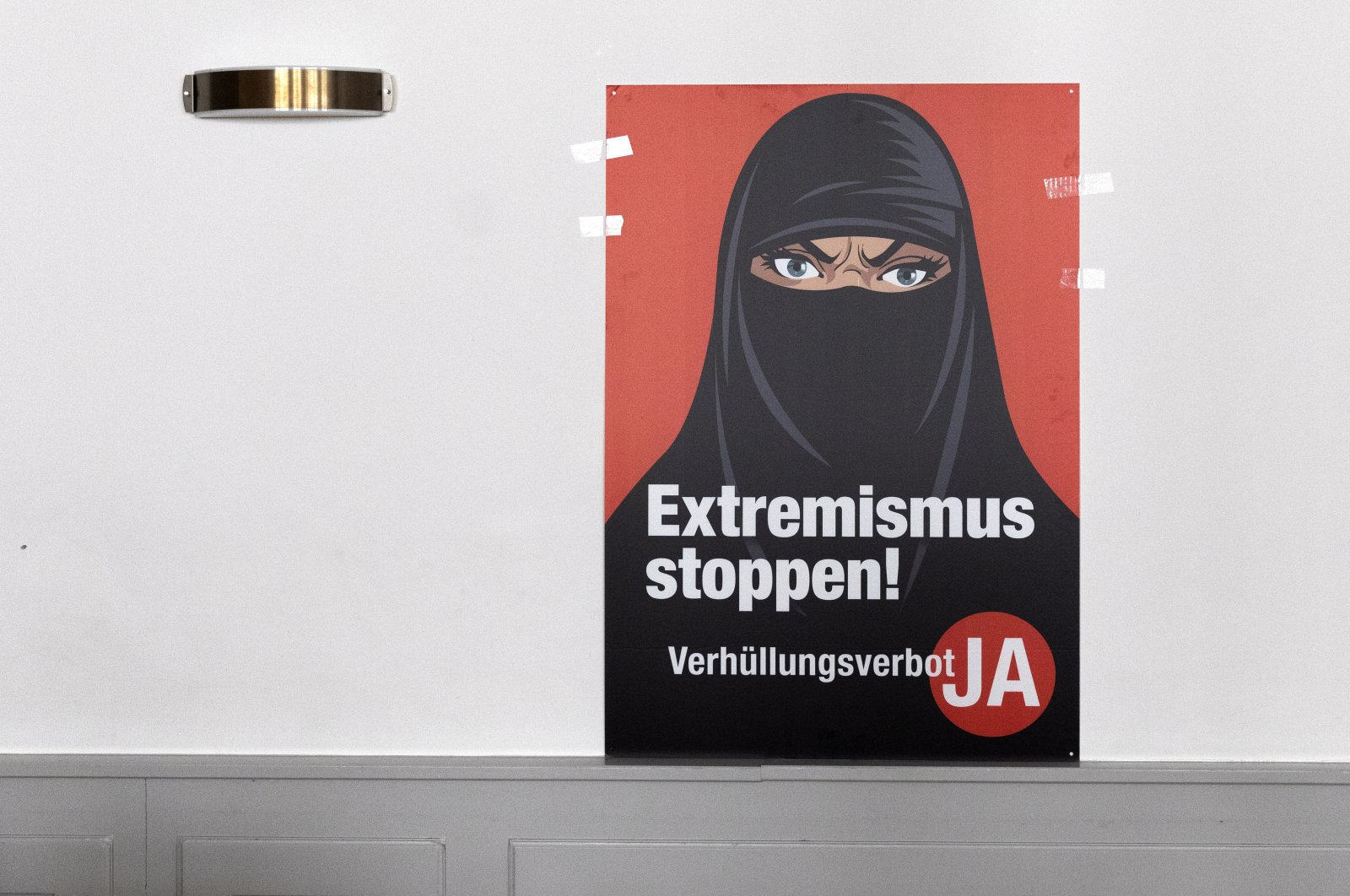 """A poster that says """"Stop Extremism"""" hangs on a wall at the meeting place of the supporters of the burqa ban initiative, in Bern, Switzerland, March 7, 2021. (EPA Photo)"""