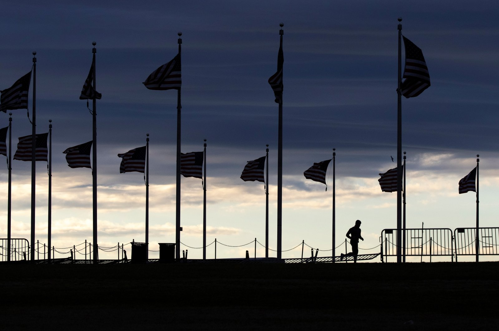 A pedestrian jogs around the Washington Monument at dusk in Washington, U.S., Feb. 16, 2021. (Reuters)