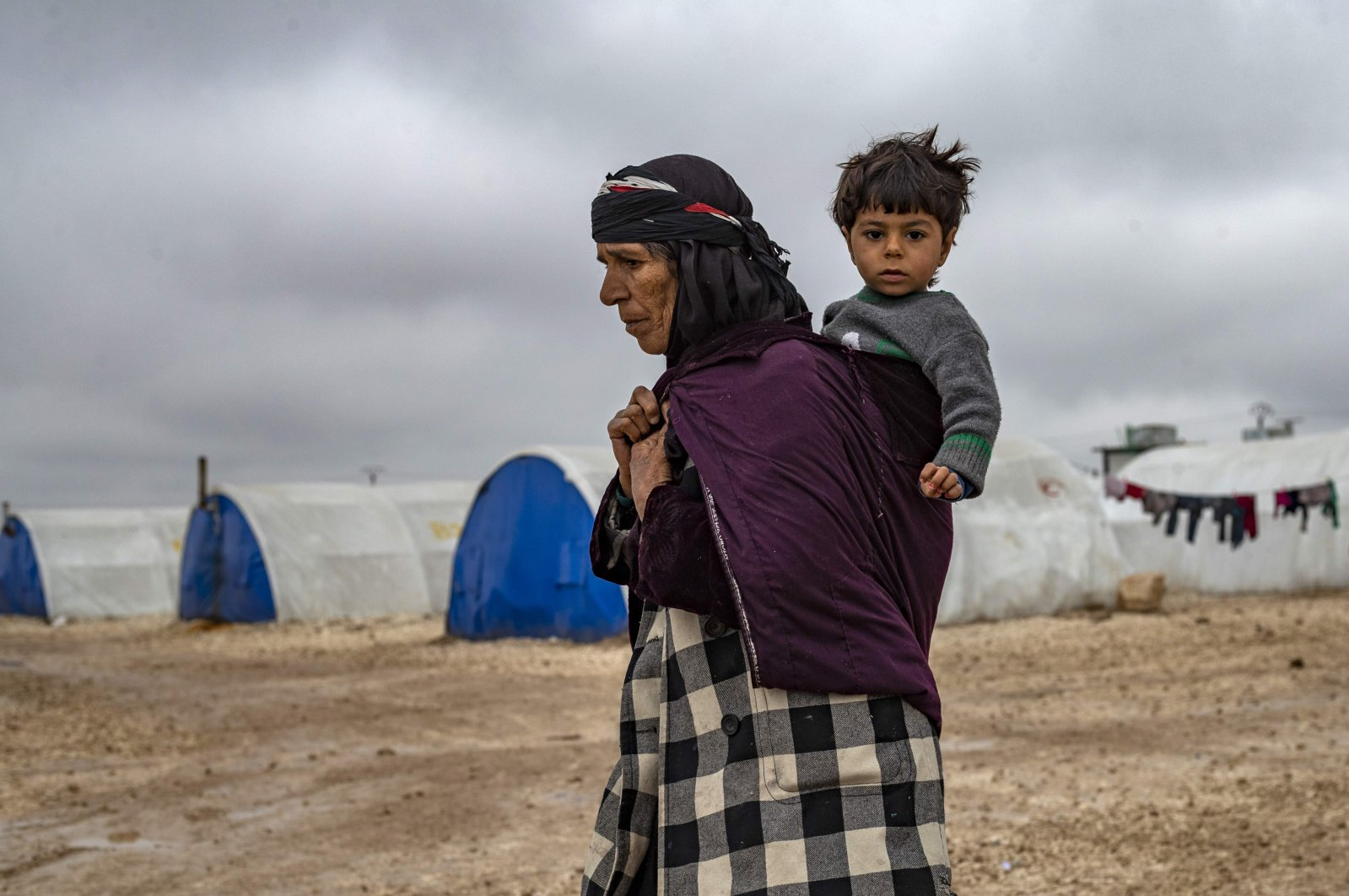 An elderly displaced Syrian woman carries a child in the Washukanni Camp for internally displaced people near al-Hasakah in northeastern Syria on Feb. 17, 2020. (AFP File Photo)
