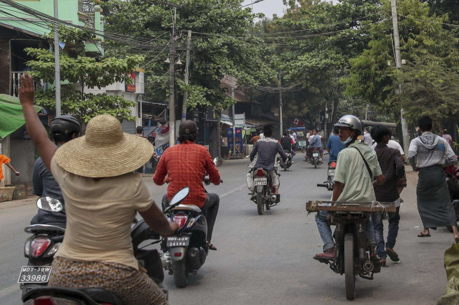 A woman on a motorbike flashes a three-fingered salute as a group of people flee after seeing the arrival of a convoy of soldiers and police officers to remove makeshift barricades made by anti-coup protesters in Mandalay, Myanmar, March 11, 2021. (AP Photo)