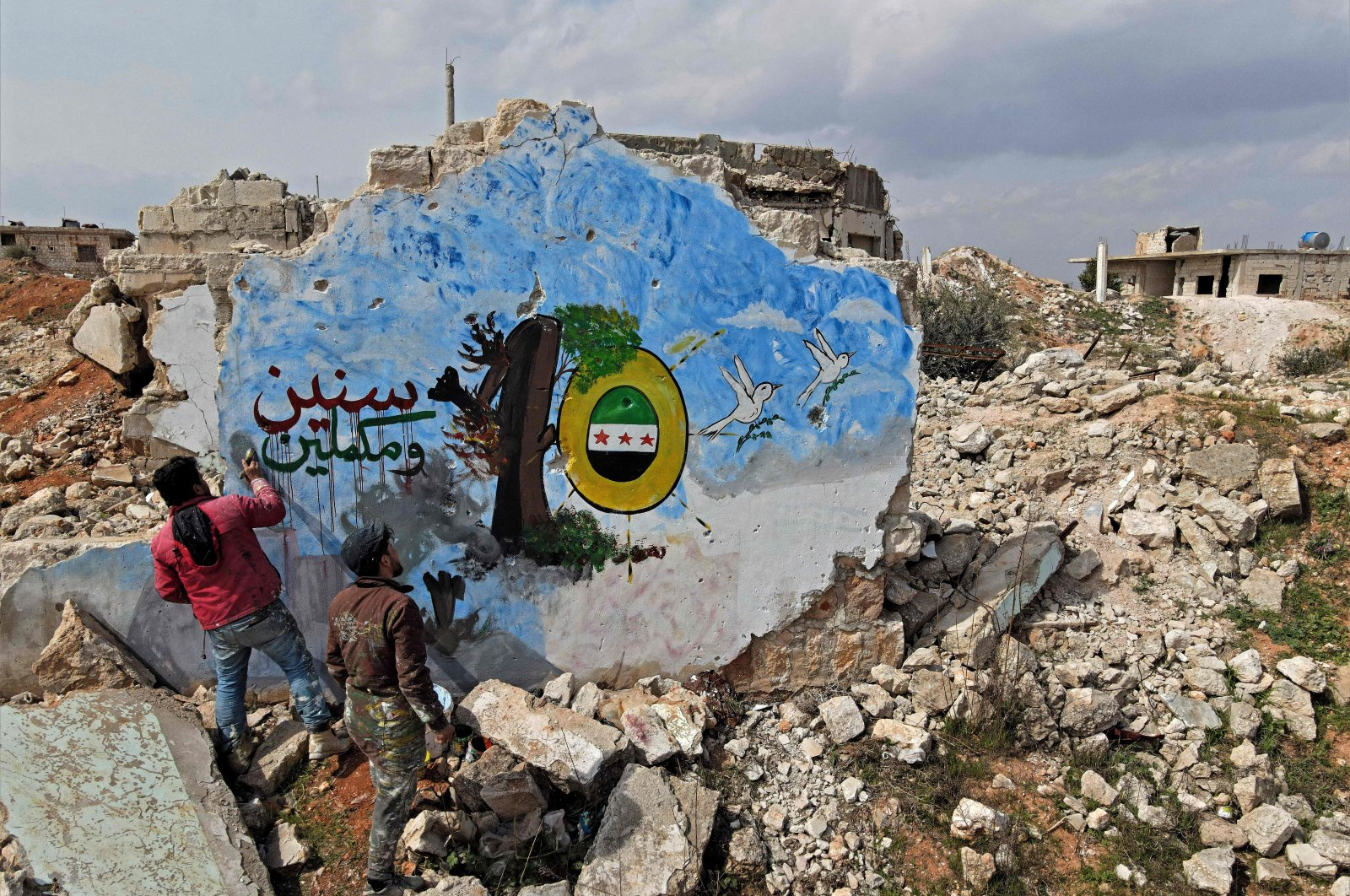 Syrians paint a mural on the remains of a building to mark 10 years of the Syrian war, in the opposition-held town of Binnish in Syria's northwestern province of Idlib, March 11, 2021. (AFP)