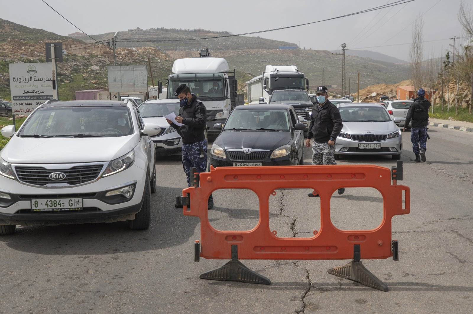 Palestinian security forces stop vehicles as part of a lockdown and quarantine measures at an entrance of the West Bank city of Ramallah, March 11, 2021. (AP Photo)