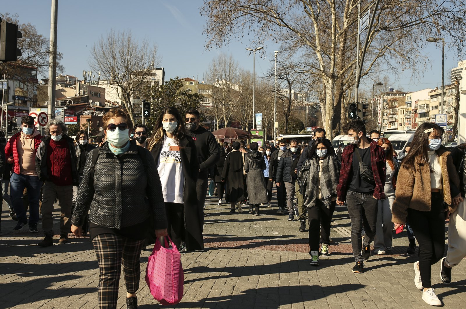 People wearing masks to help prevent the spread of the coronavirus walk in Istanbul, Friday, March 5, 2021. (AP Photo)