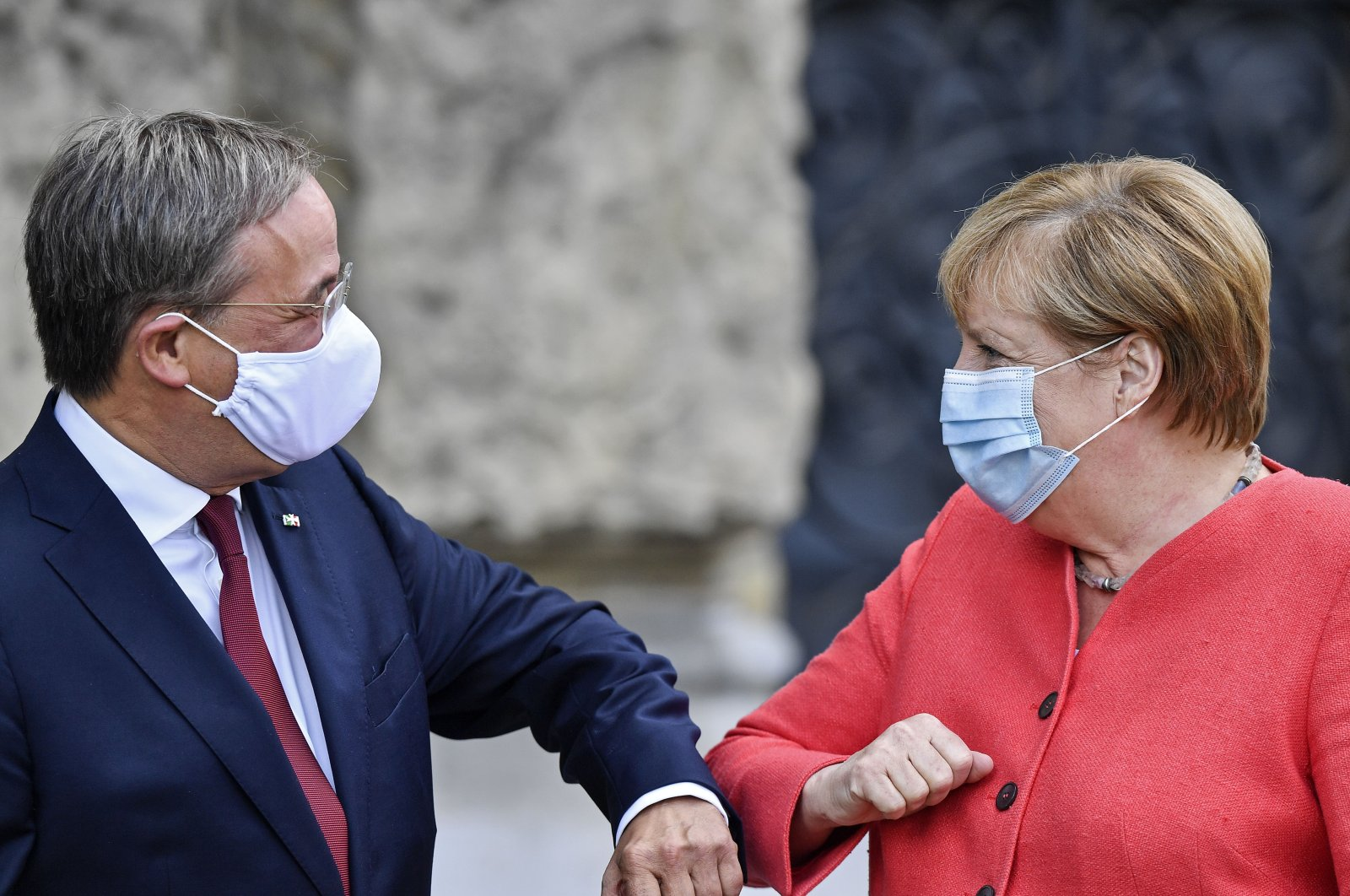 In this Tuesday, Aug. 18, 2020 file photo German Chancellor Angela Merkel, left, and her successor as chairman of the German Christian Democratic Union, CDU, Armin Laschet, right, greet each other during a meeting in Duesseldorf, Germany. (AP File Photo)