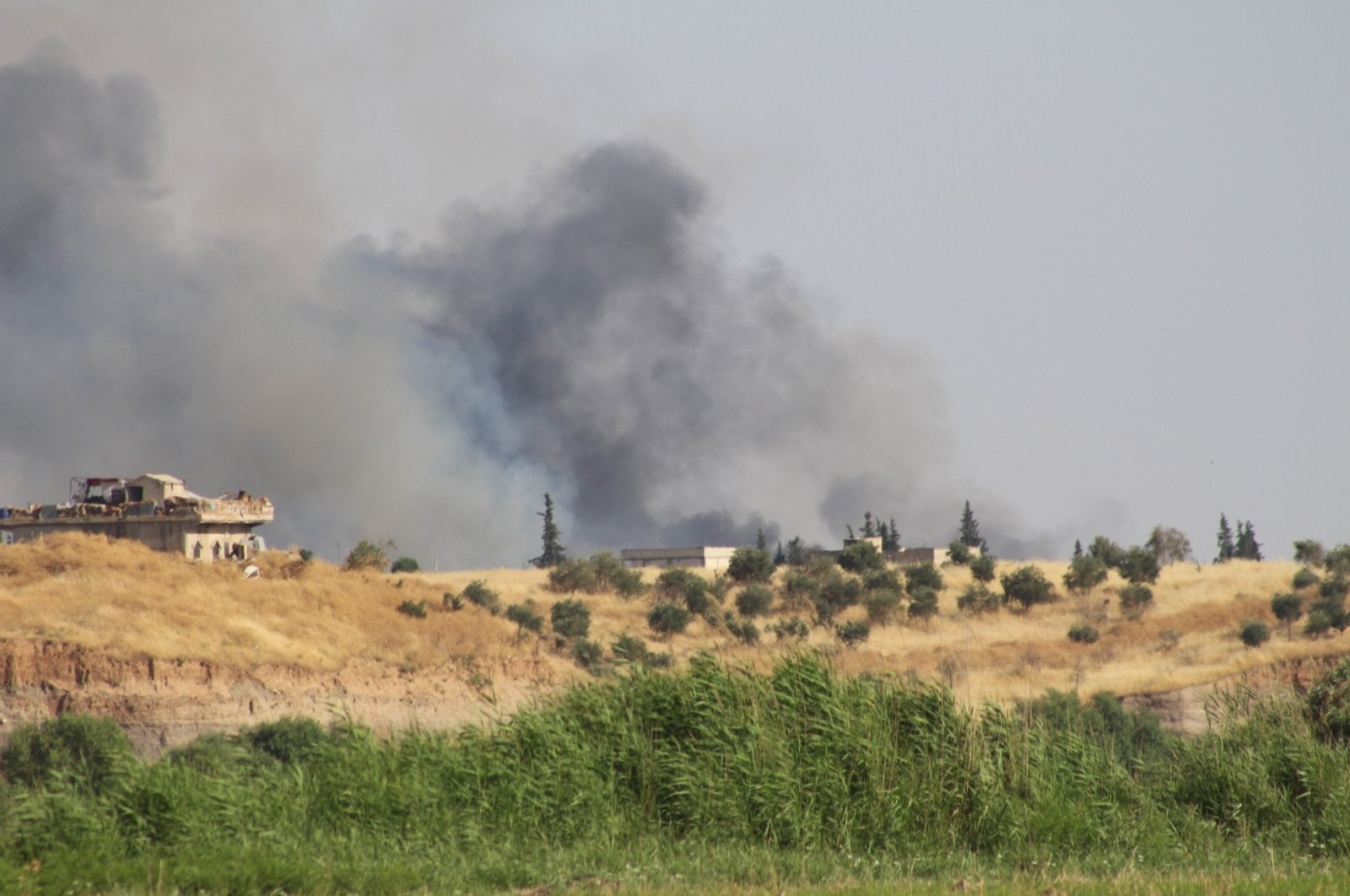 Smoke is seen in a village east of Syria's Jarablus on June 26, 2019 (AA File Photo)