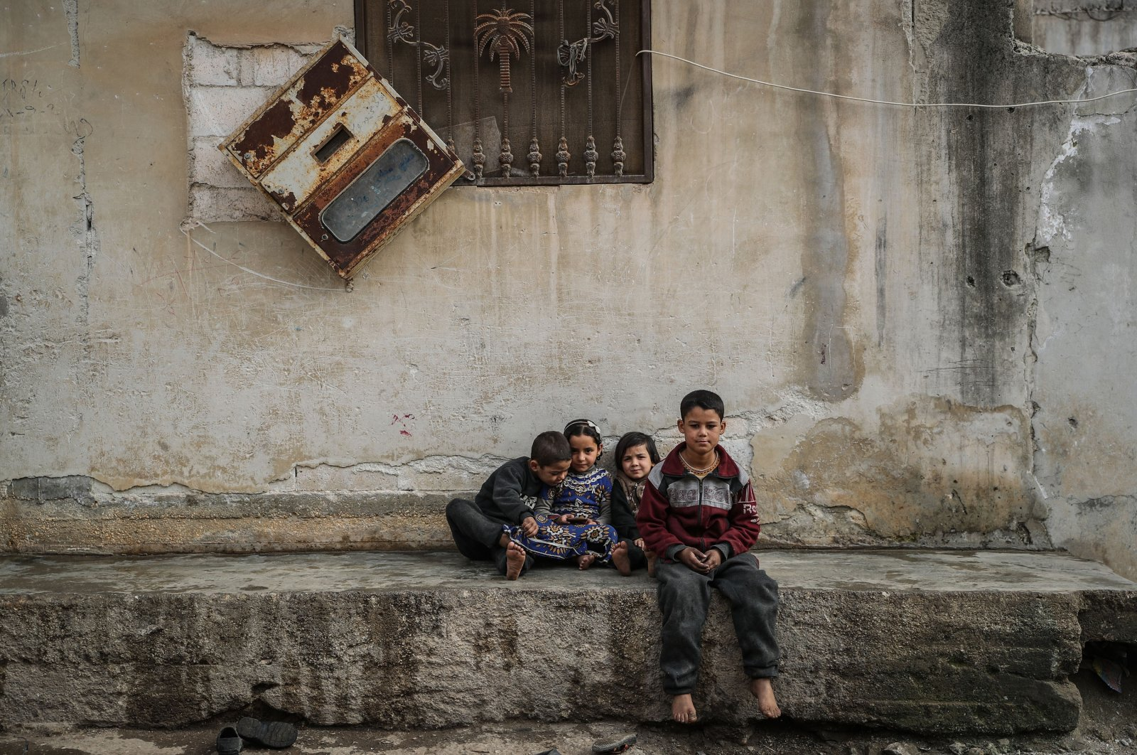 Syrian children sit outside their home in northwestern Idlib's village of Afes after residents displaced by intense Syrian regime bombings start to return, Syria, Jan. 2, 2021. (Getty Images)