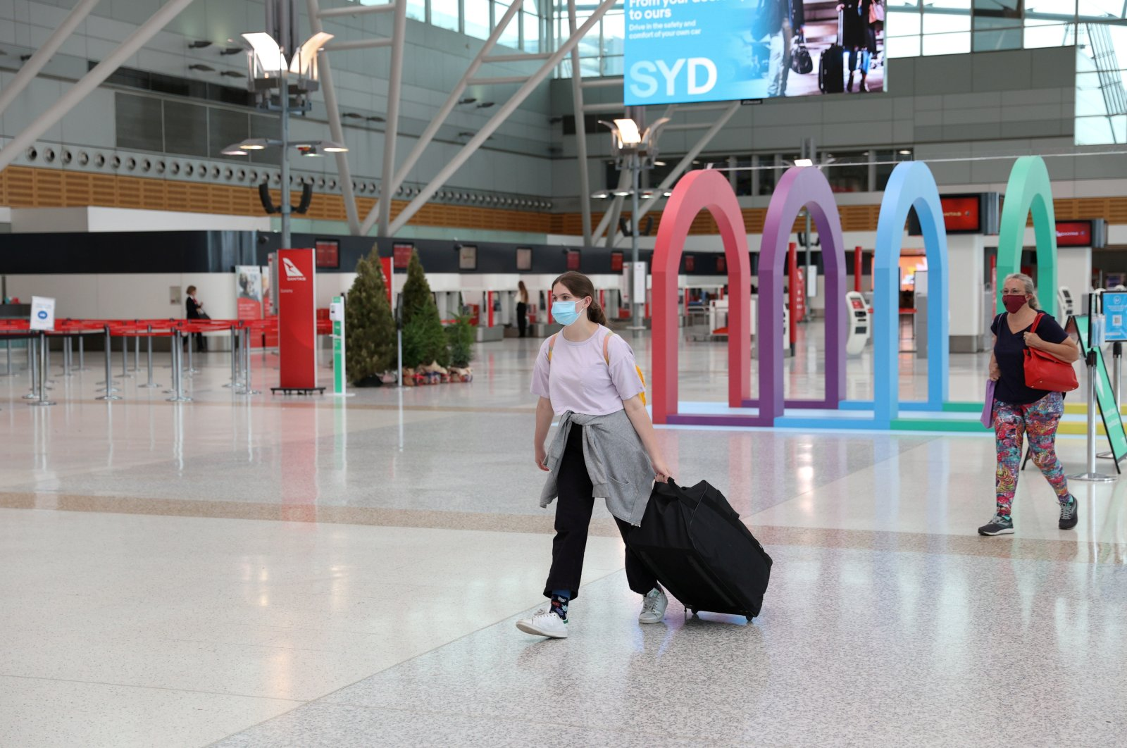People wearing masks walk through a mostly empty domestic terminal at Sydney Airport in Sydney, Australia, Dec. 21, 2020.   (Reuters Photo)