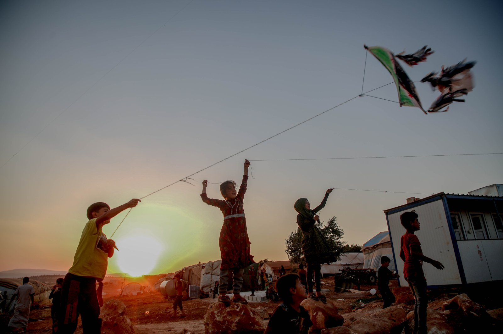 Syrian children fly kites at sunset in a camp for the displaced, Idlib, northwestern Syria, July 6, 2020. (Photo by Getty Images)