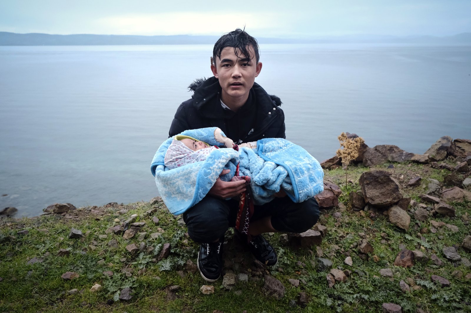 A migrant holding a baby pauses on the side of the road while walking to the village of Skala Sikaminias on the Greek island of Lesbos after crossing the Aegean sea from Turkey on a dinghy,  March 5, 2020. (AP)