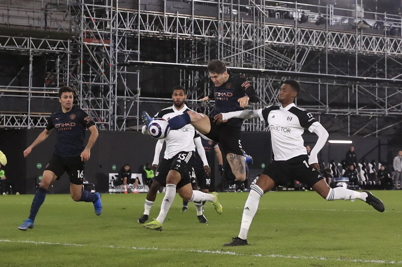 Manchester City's John Stones (2nd R) scores the opening goal during an English Premier League soccer match between Fulham and Manchester City at the Craven Cottage stadium in London, England, March 13, 2021. (AP Photo)
