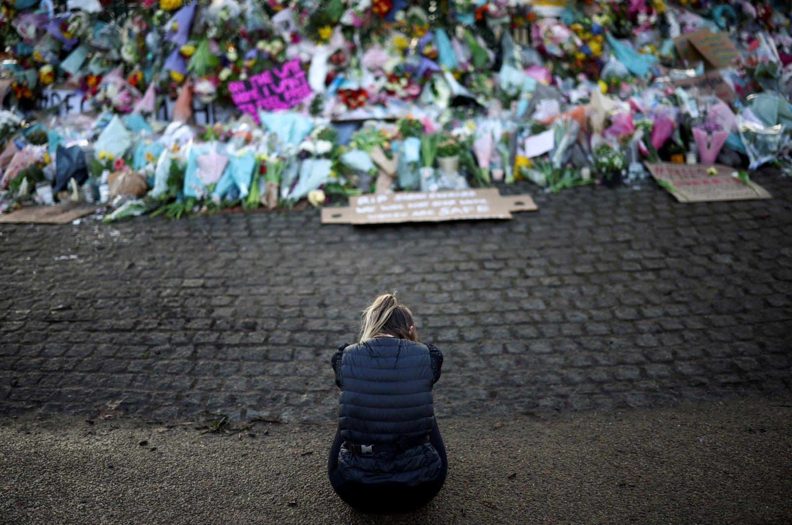 A mourner sits in front of a memorial site at the Clapham Common Bandstand, following the kidnap and murder of Sarah Everard, in London, Britain, March 14, 2021. (Reuters Photo)
