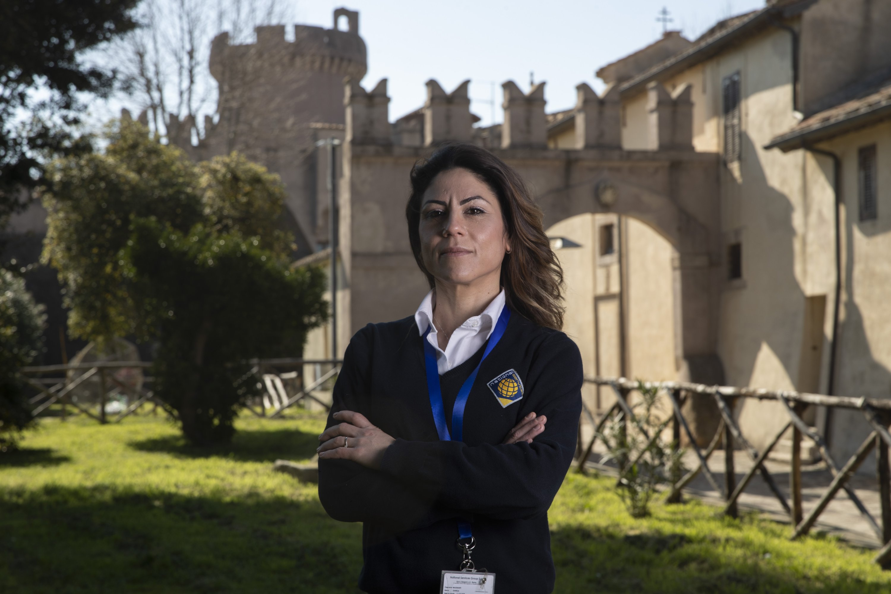 Daniela Magnanti poses in front of the Santa Severa castle where she has a part-time work at the check-in desk of a hotel that opened in the castle, Rome, Italy, March 5, 2021. (AP Photo)