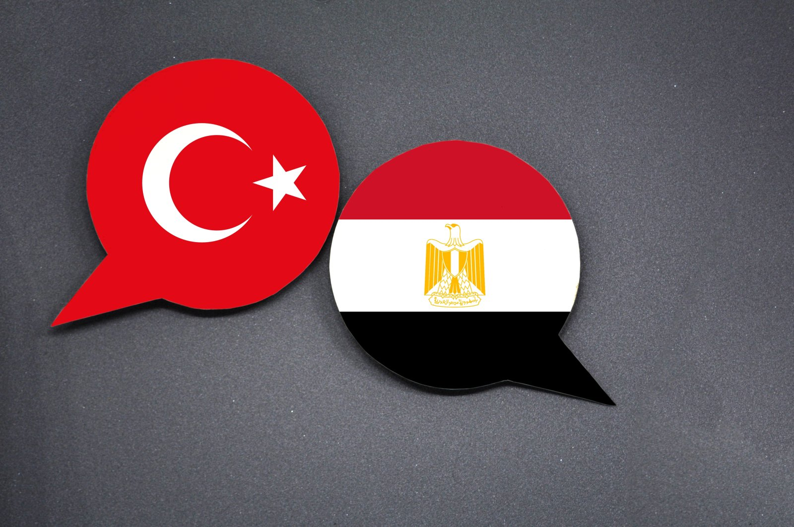 In this illustration, the flags of Turkey and Egypt are seen as two speech bubbles on a dark gray background. (Photo by Shutterstock)