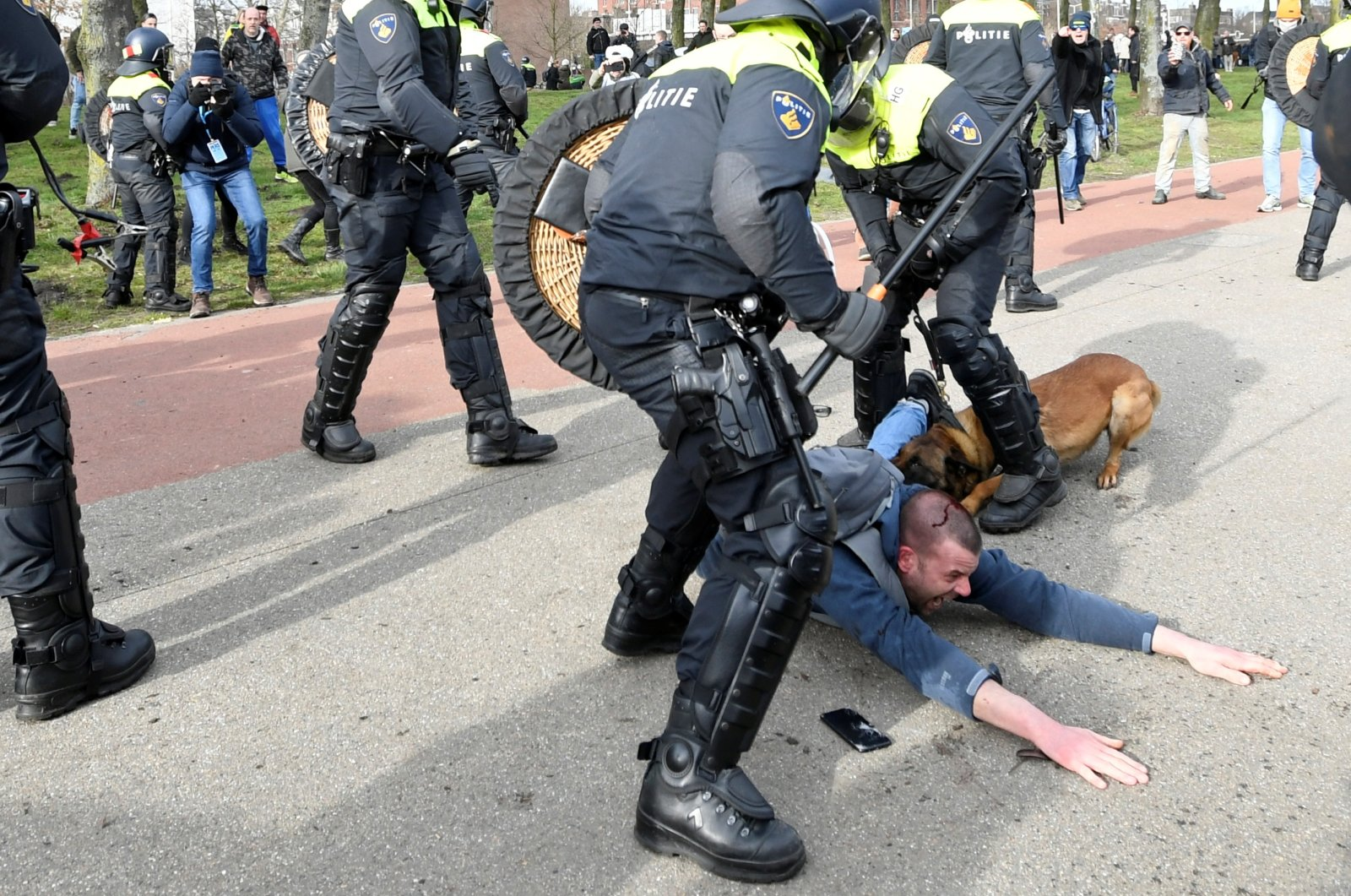 A demonstrator is bitten by a police dog while fighting with police during a protest against the coronavirus disease (COVID-19) restrictions in The Hague, Netherlands, March 14, 2021. (Reuters Photo)