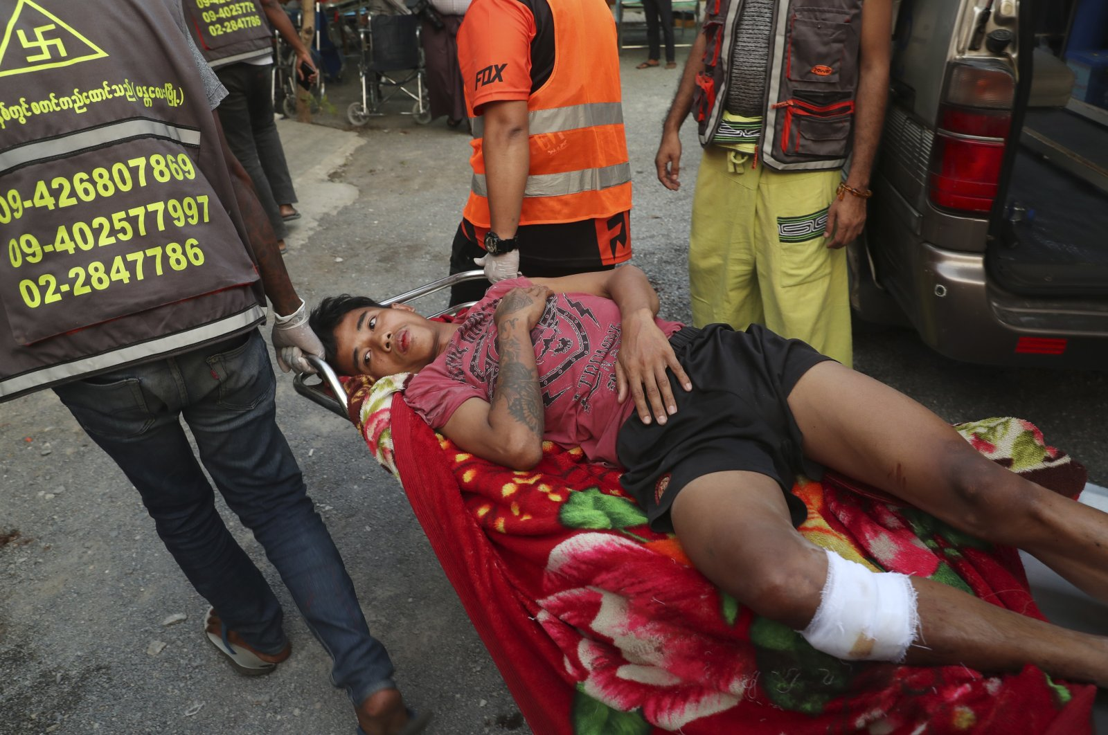 An injured man lies on a stretcher being carried by members of a volunteer rescue team in Mandalay, Myanmar Sunday, March 14, 2021. (AP Photo)