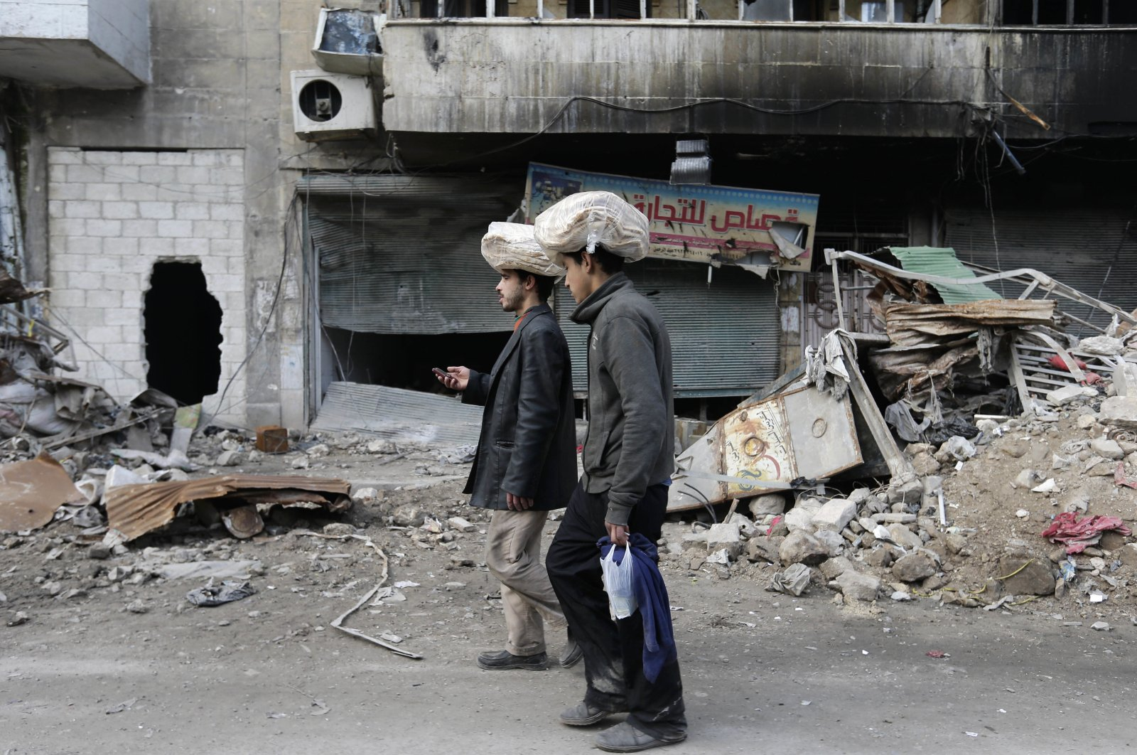 Syrian men carry bags of bread on their heads while walking back to their homes in the once opposition-held Bustan al-Qasr neighborhood in eastern Aleppo, Syria, Jan. 20, 2017. (AP Photo)