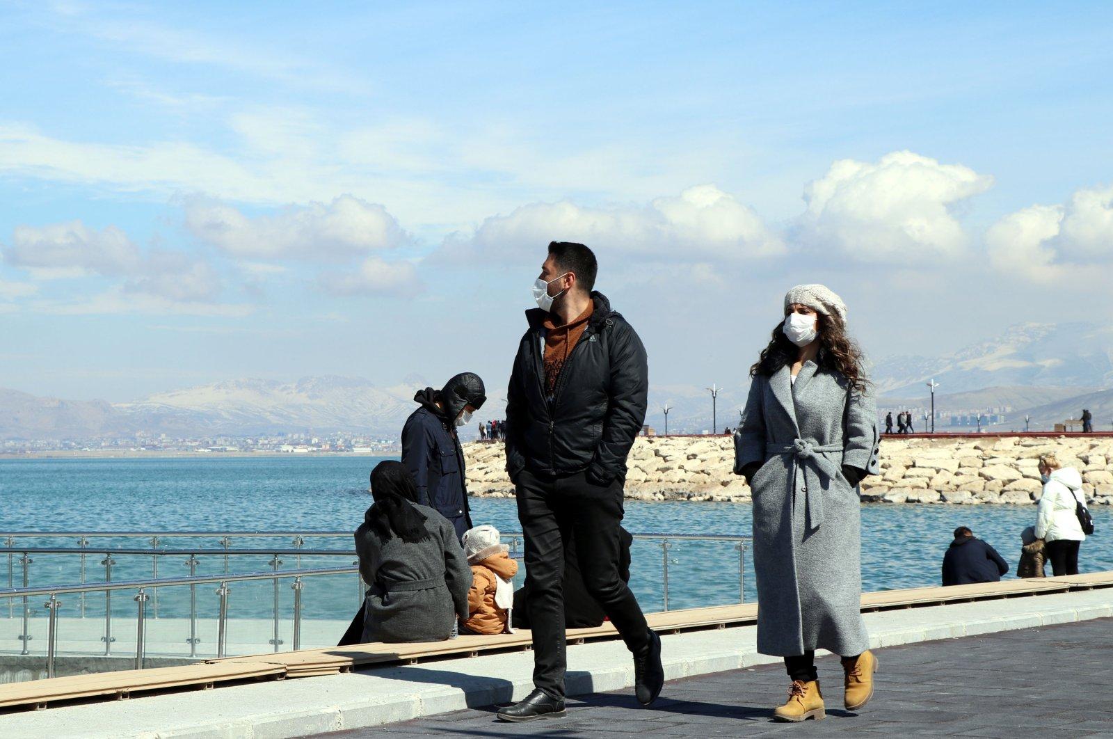 People wearing protective masks walk on the shore of Lake Van, in Van, eastern Turkey, March 14, 2021. (DHA PHOTO)