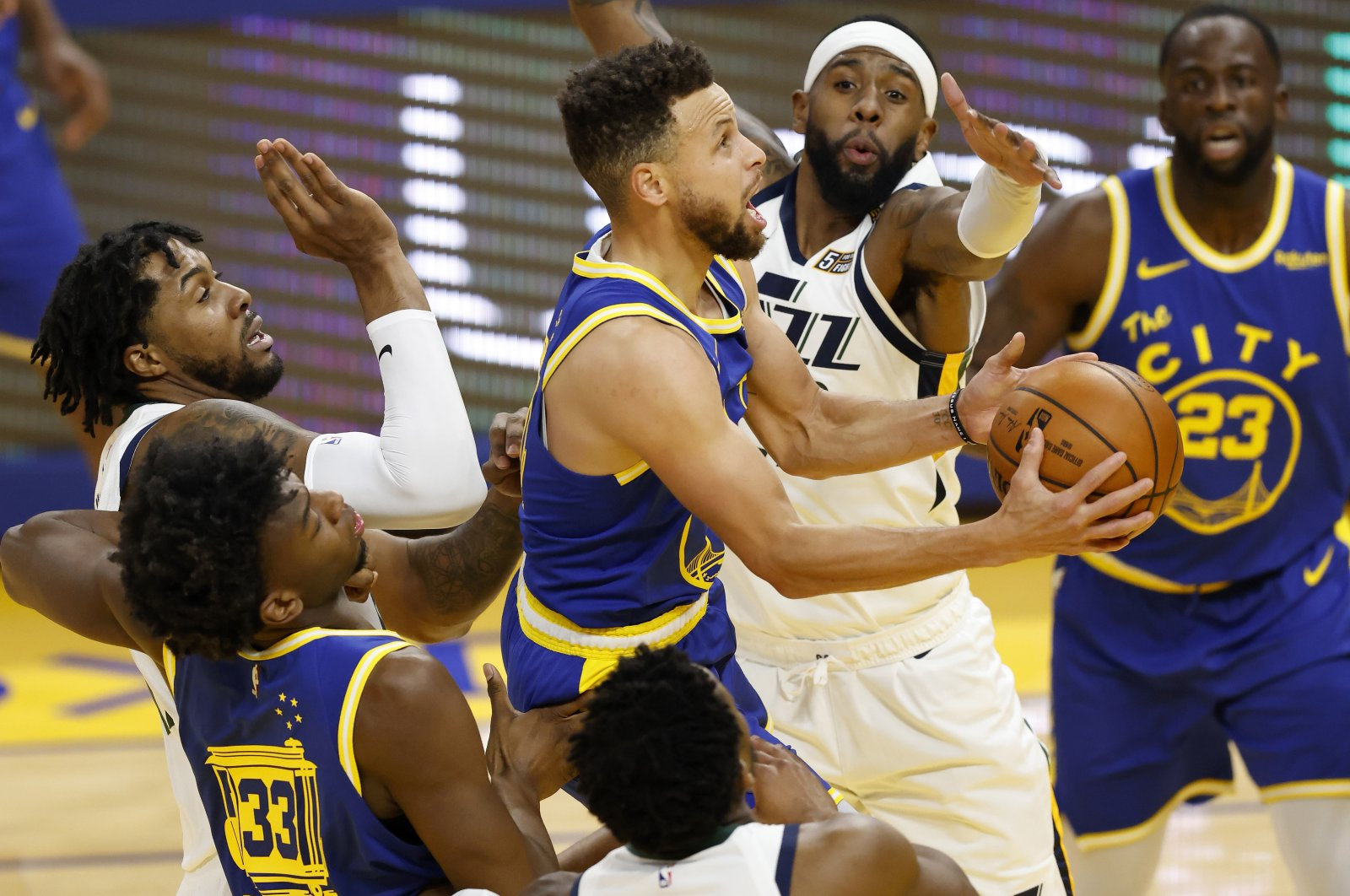 Golden State Warriors guard Stephen Curry (C) goes to the basket as Utah Jazz guard Jordan Clarkson (2nd R), Utah Jazz center Derrick Favors (L) and Utah Jazz guard Donovan Mitchell defend during an NBA game at Chase Center in San Francisco, California, March 14, 2021. (EPA Photo)