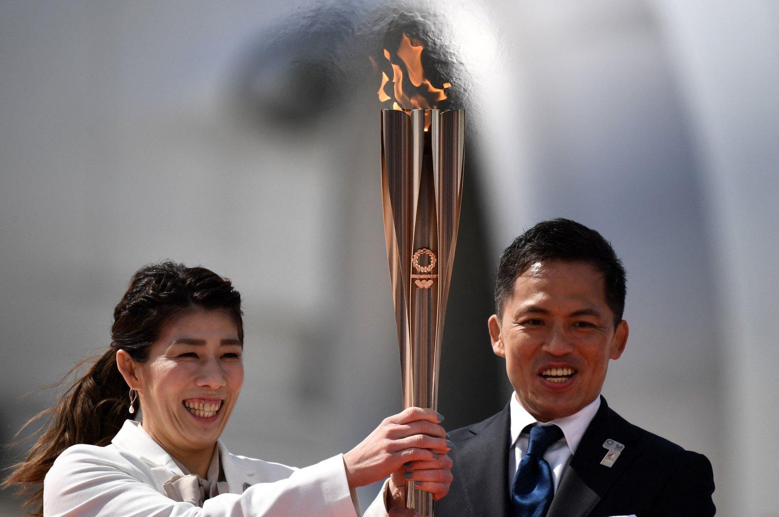 Japanese three-time Olympic gold medallists Saori Yoshida (L) and Tadahiro Nomura (R) holdthe Tokyo 2020 Olympic Torch, Higashimatsushima, Japan, March 20, 2020. (AFP Photo)