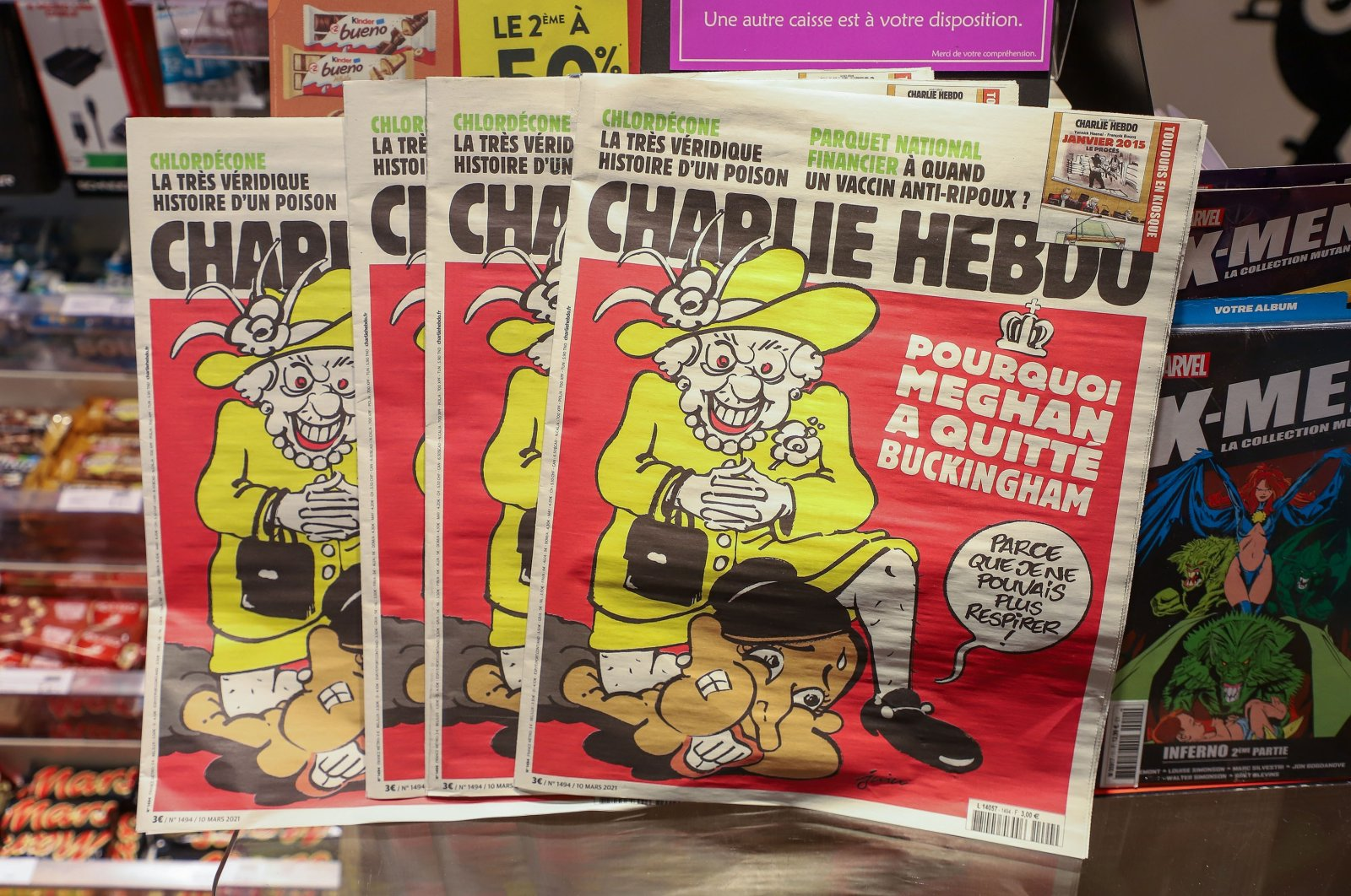 French satirical weekly Charlie Hebdo's edition displays a cover with a satirical drawing representing Queen Elizabeth kneeling on Duchess of Sussex Meghan's neck, echoing George Floyd's killing, Paris, France, March 15, 2021. (Getty Images)