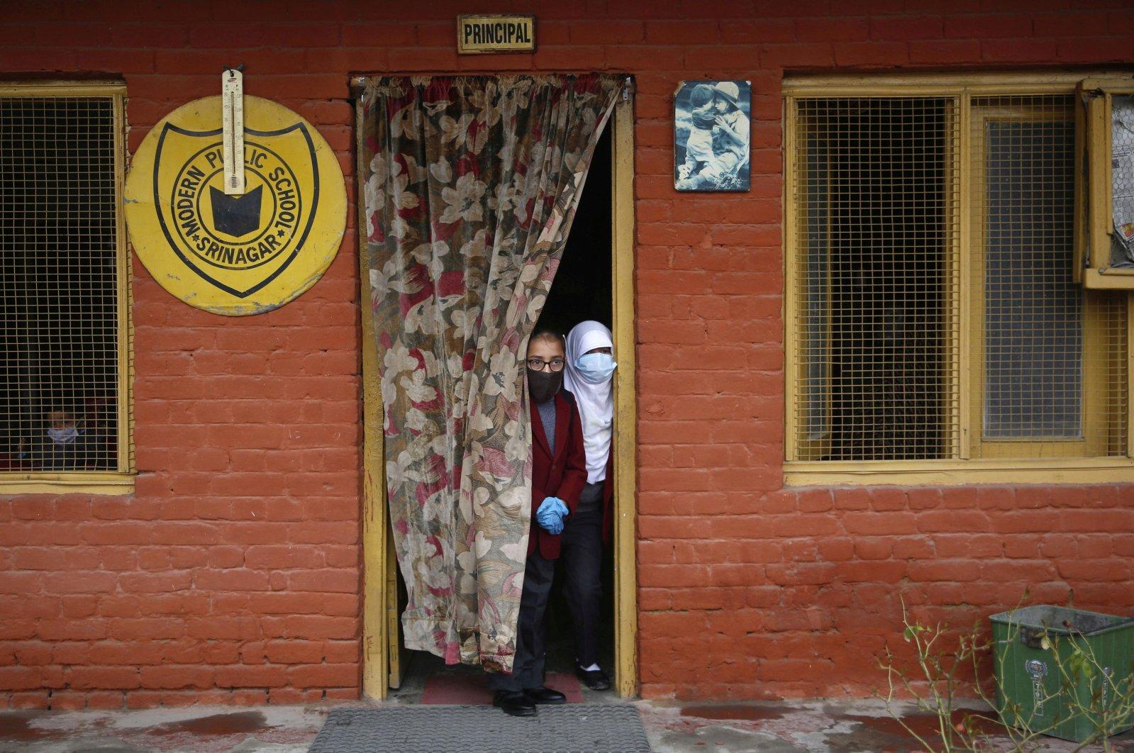 Students peer through a door as they attend school, in Srinagar, Indian Kashmir, March 15, 2021. (EPA)