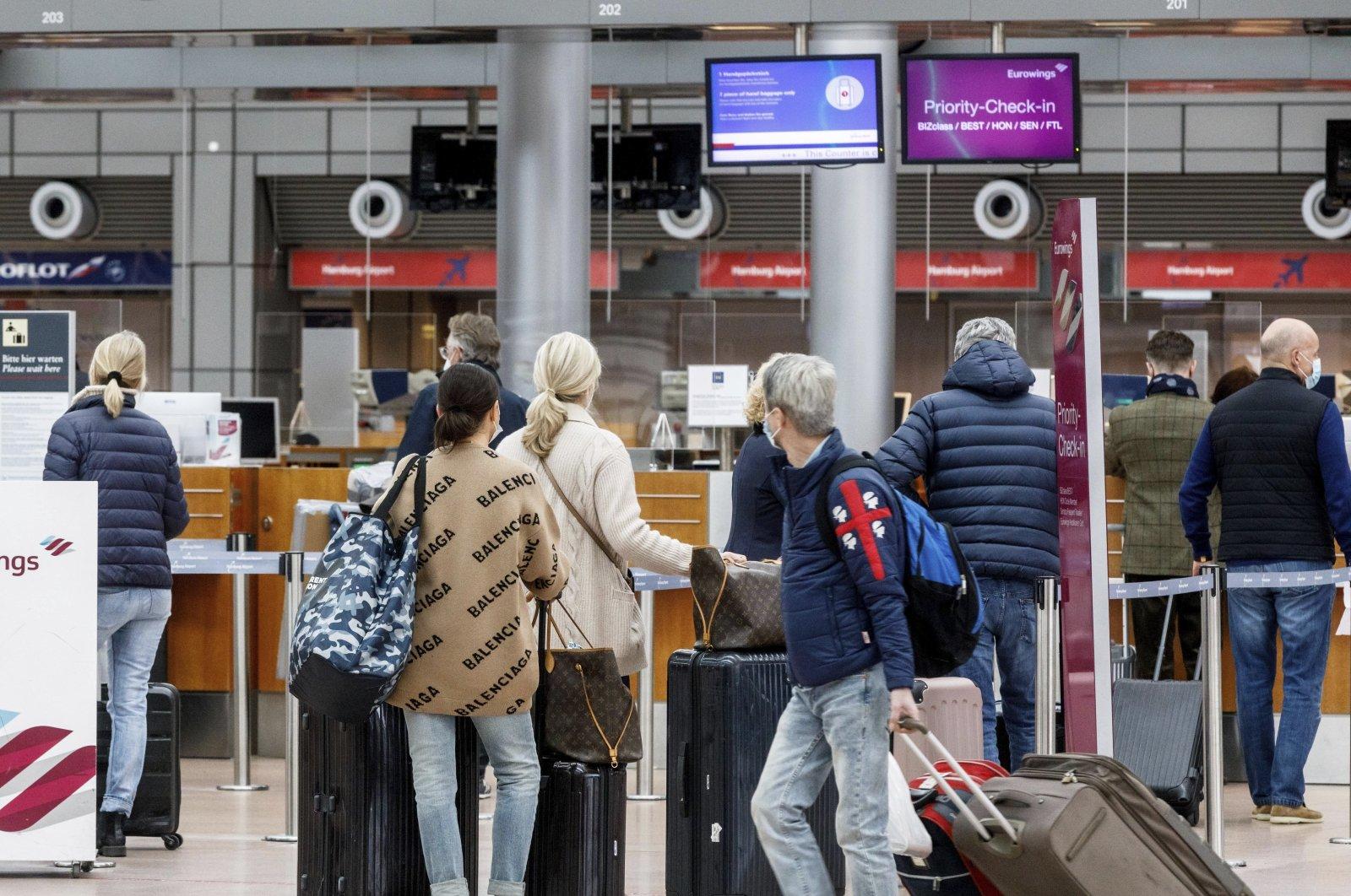 Passengers check in at Hamburg Airport, Germany, March 14, 2021. (AP Photo)