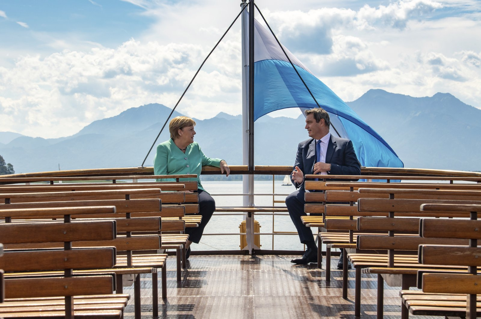 German Chancellor Angela, left, and Markus Soeder, right, Governour of the German state of Bavaria, talk during a boat tour in Priem Am Chiemsee, Germany, July 14, 2020. (AP Photo)