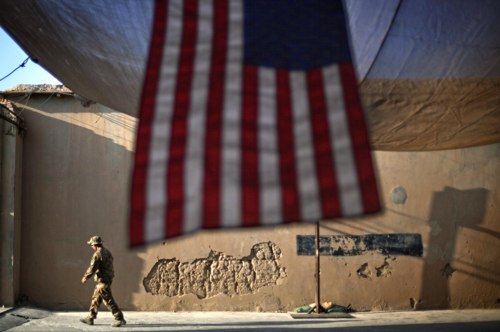 A U.S. Army soldier walks past an American flag hanging in preparation for a ceremony commemorating the tenth anniversary of the 9/11 attacks, in Kunar province, Afghanistan, Sept. 11, 2011. (AP Photo)