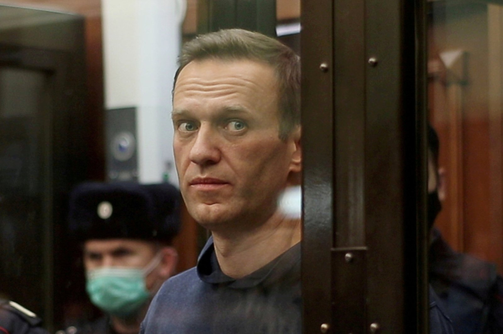 A still image taken from video footage shows Russian opposition leader Alexei Navalny, who is accused of flouting the terms of a suspended sentence for embezzlement, inside a defendant dock during the announcement of a court verdict in Moscow, Russia, Feb. 2, 2021. (Press service of Simonovsky District Court via Reuters)
