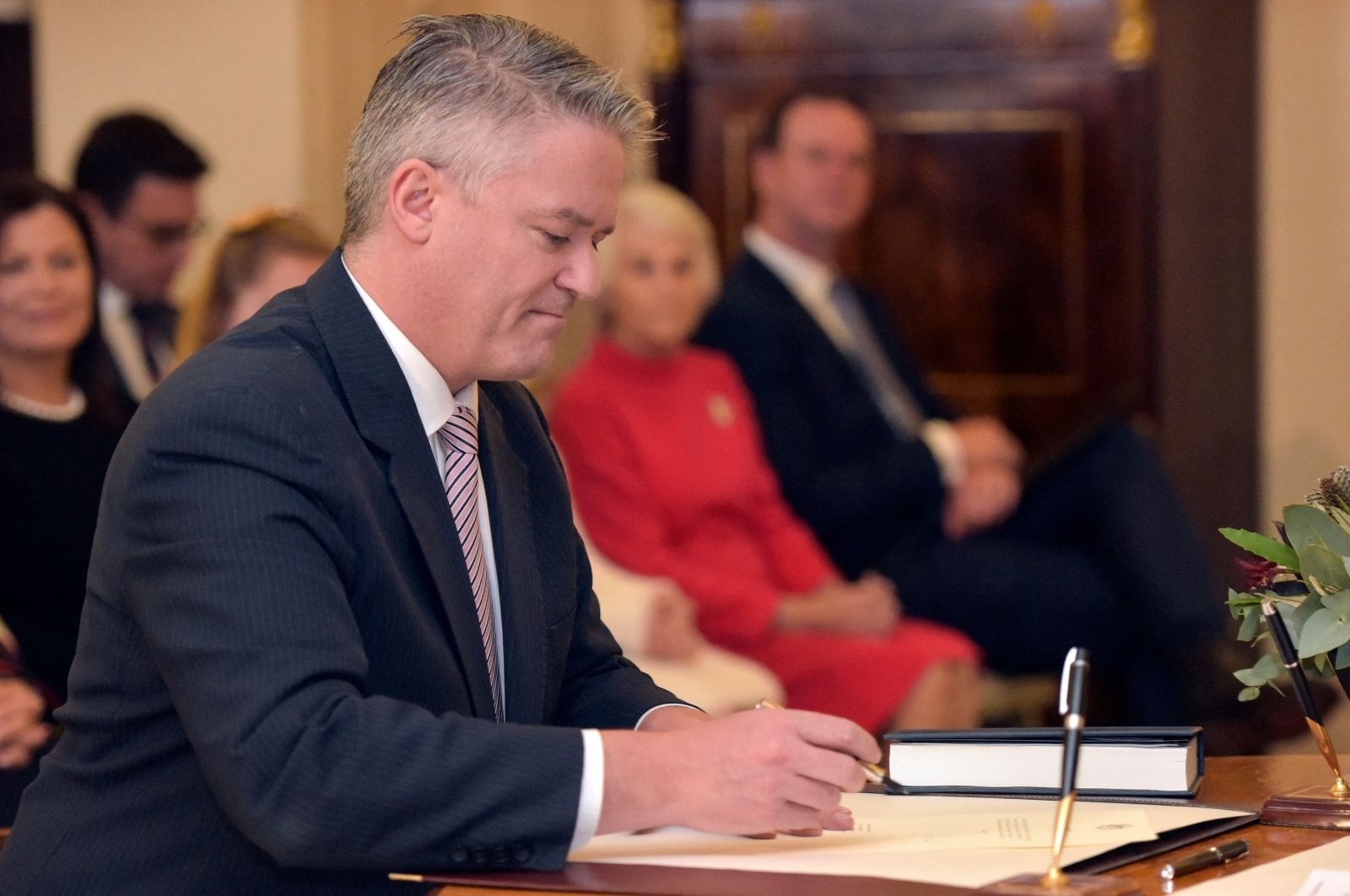 Mathias Cormann signs a document during an oath-taking ceremony at the Government House in Canberra on May 29, 2019. (AFP File Photo)