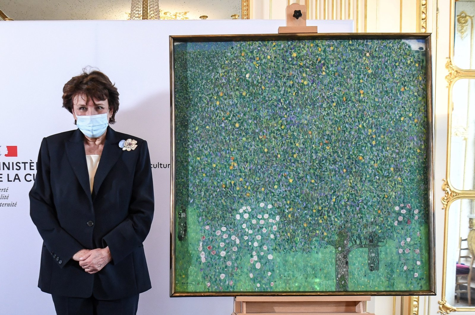 "French Culture Minister Roselyne Bachelot poses next to a spoiled oil painting by Gustav Klimt painted in 1905 called ""Rosebushes under the Trees,"" during a ceremony at the Orsay museum in Paris, France, March 15, 2021. (AP Photo)"