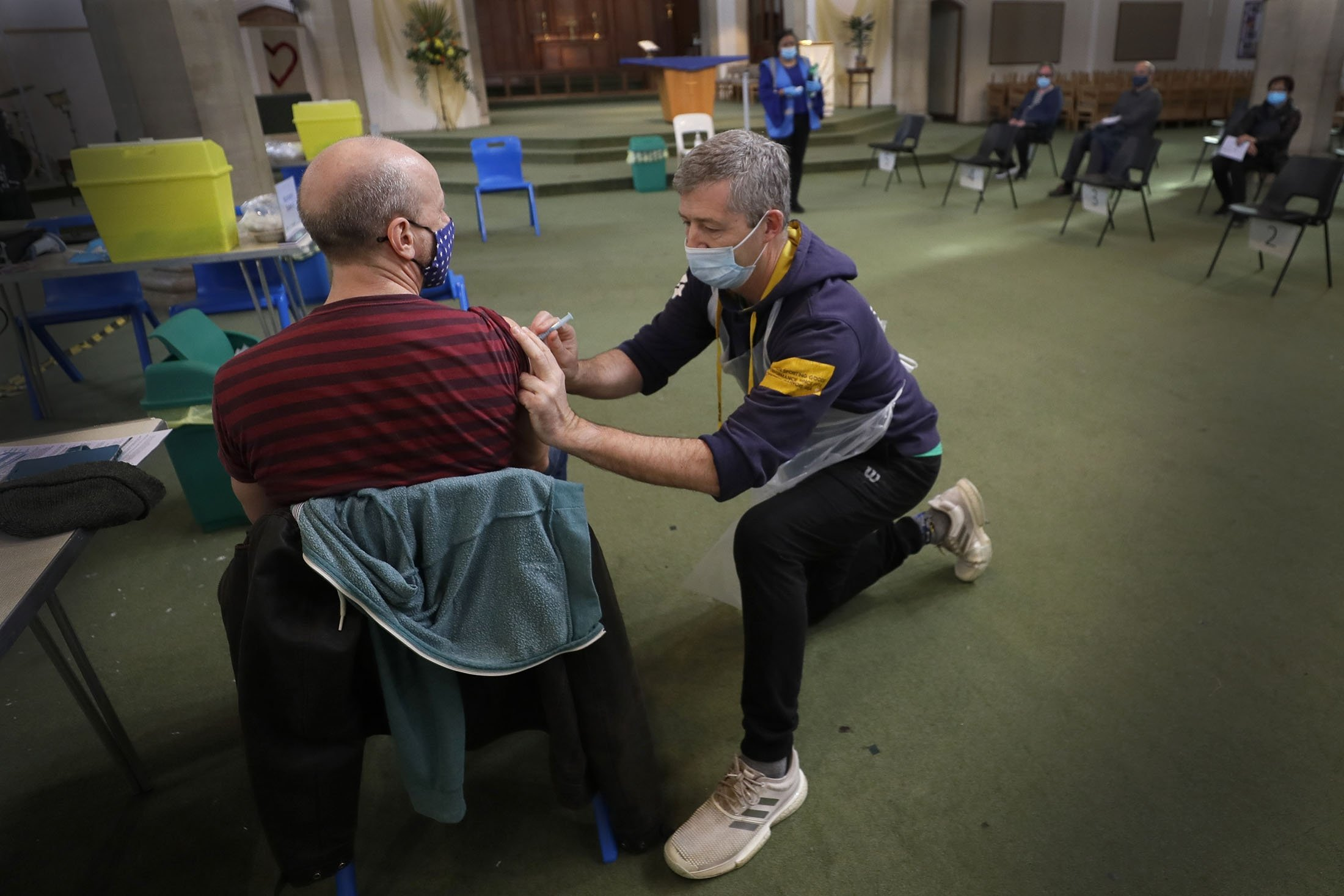 A St Johns Ambulance vaccinator gives the AstraZeneca vaccine at St John's Church, in Ealing, London, Tuesday, March 16, 2021. (AP Photo)