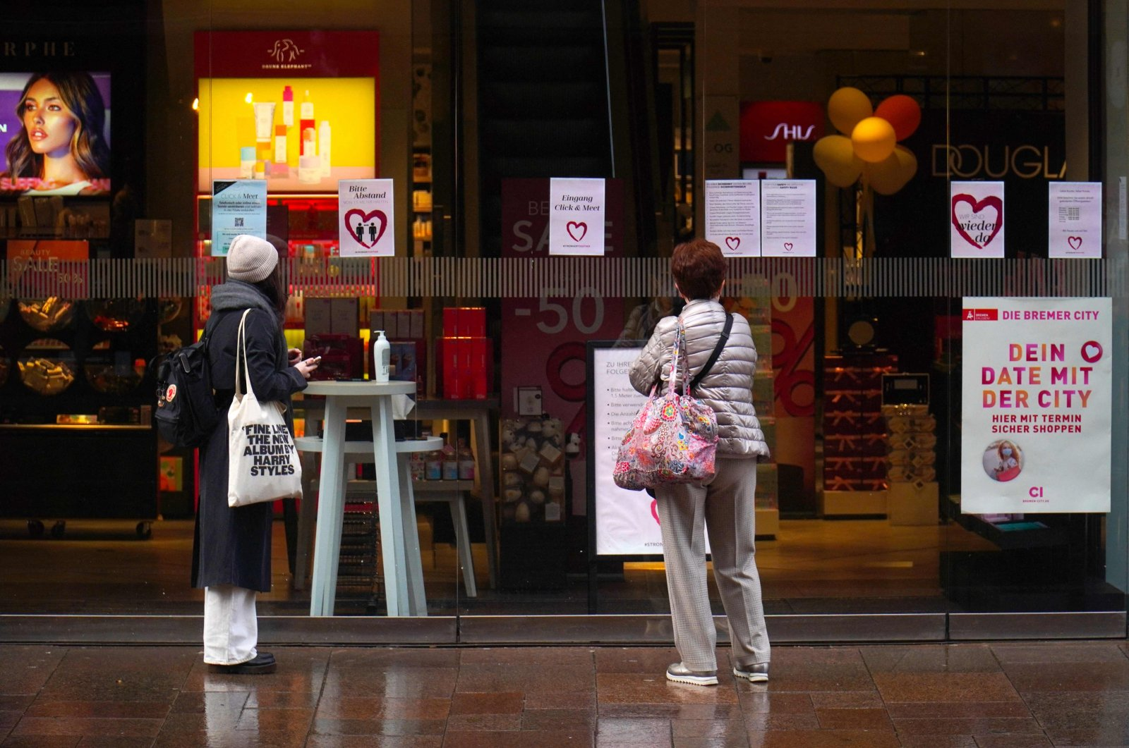 """Customers stand in front of the entrance of a shop with notes for """"click and meet"""" on a shopping street, during the ongoing coronavirus (COVID-19) pandemic, in the center of Bremen, Germany, on March 15, 2021. (AFP Photo)"""