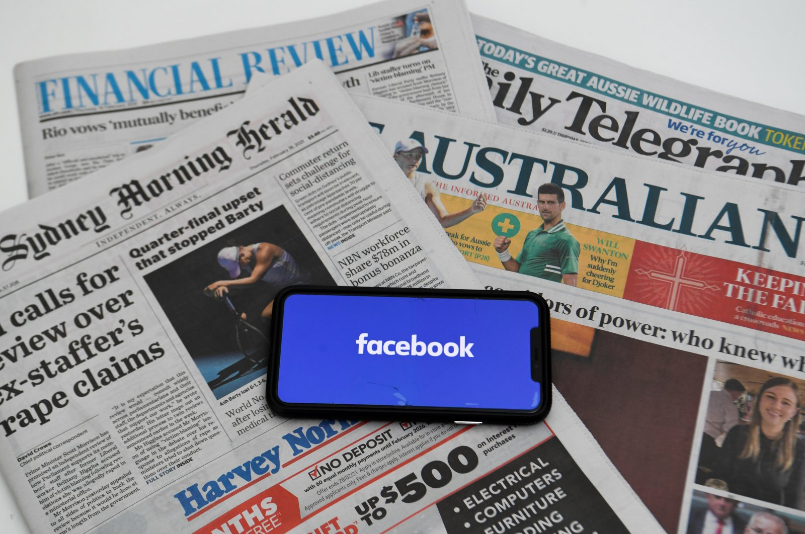 """An illustration image shows a phone screen with the """"Facebook"""" logo and Australian newspapers in Canberra, Australia, Feb. 18, 2021. (Reuters Photo)"""