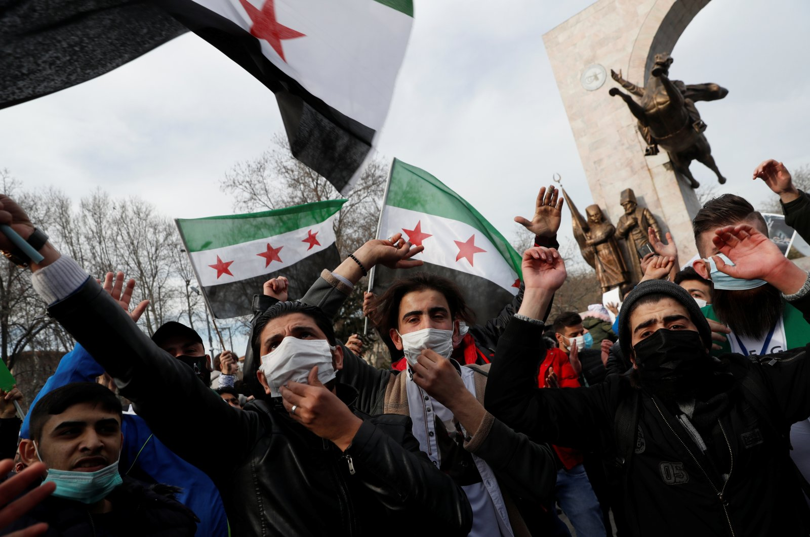 Syrians living in Turkey wave flags during a demonstration to mark the 10th anniversary of the Syrian conflict, Istanbul, Turkey, March 13, 2021. (REUTERS/Murad Sezer)