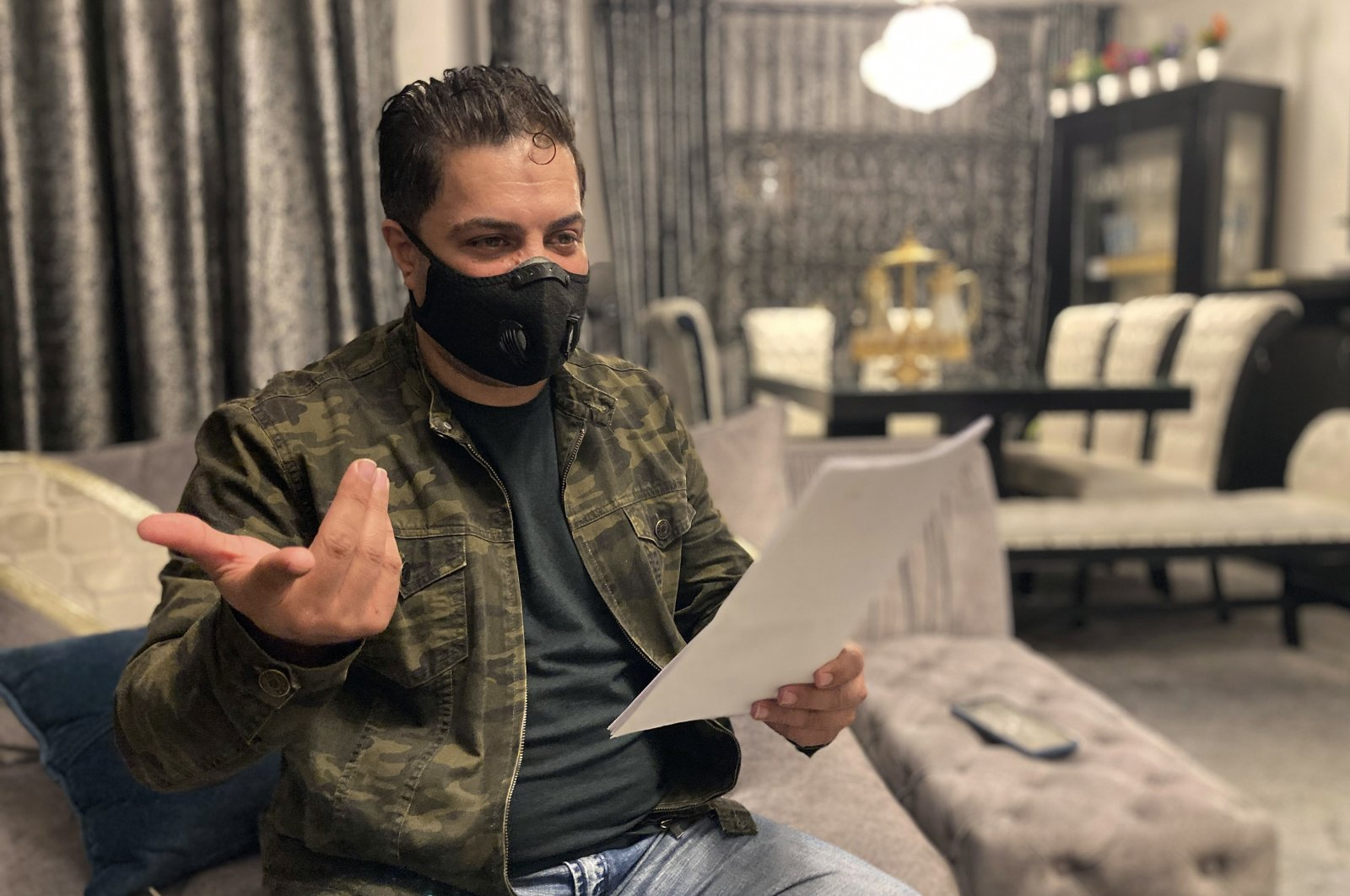 Samer Qraih, a Jordanian car dealer, sits in his apartment holding old business licenses, bank statements and documents, in Amman, Jordan, March 14, 2021. (AP Photo)