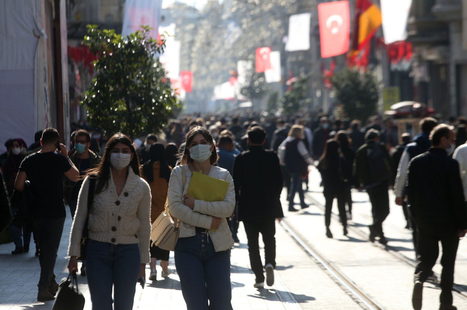 People wearing protective masks walk on Istiklal Avenue, in Istanbul, Turkey, March 15, 2021. (AA PHOTO)