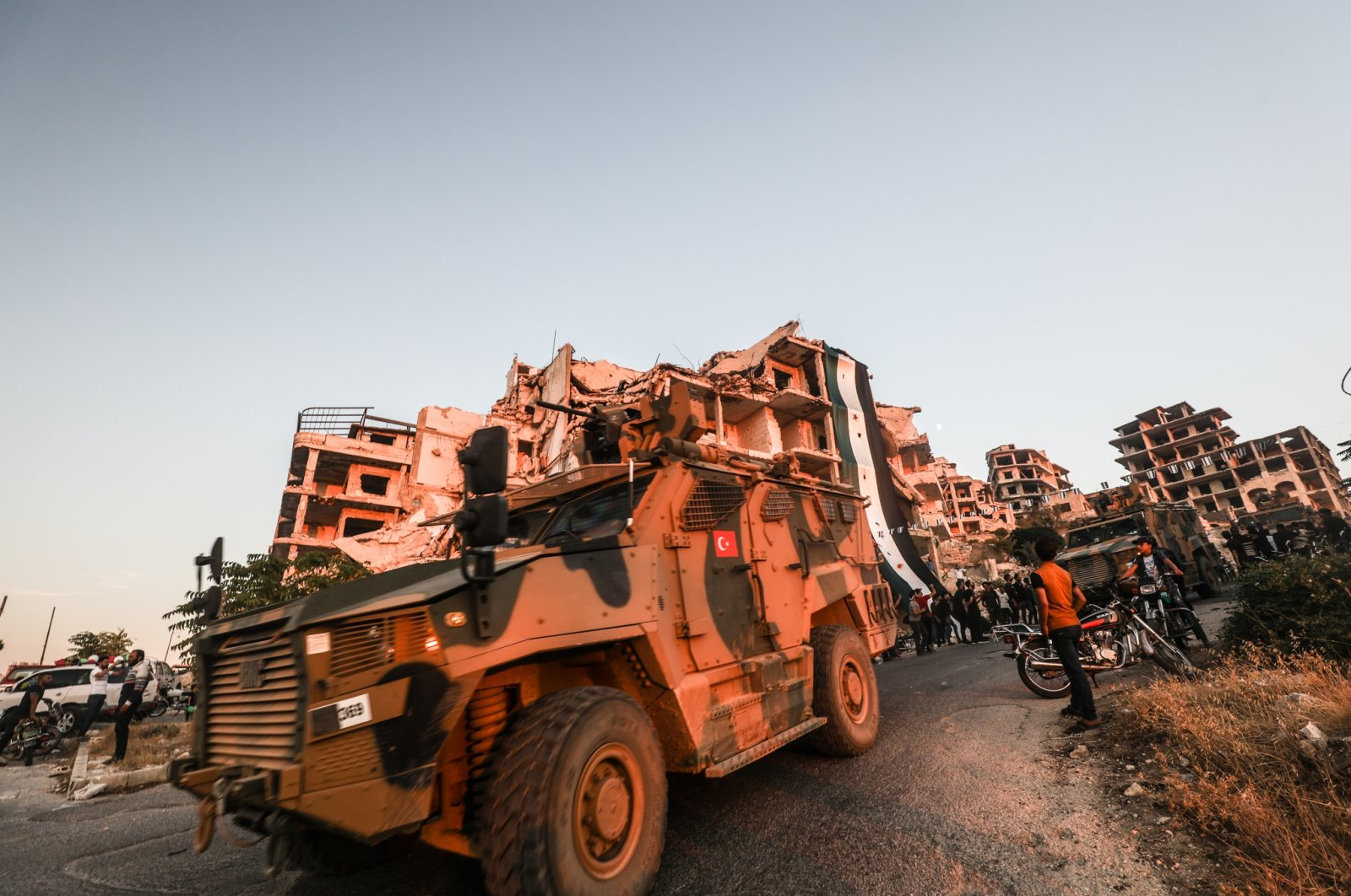 A Turkish military vehicle passes Syrians gathering in an anti-regime protest, Idlib, northern Syria, Aug. 28, 2020. (Photo by Getty Images)