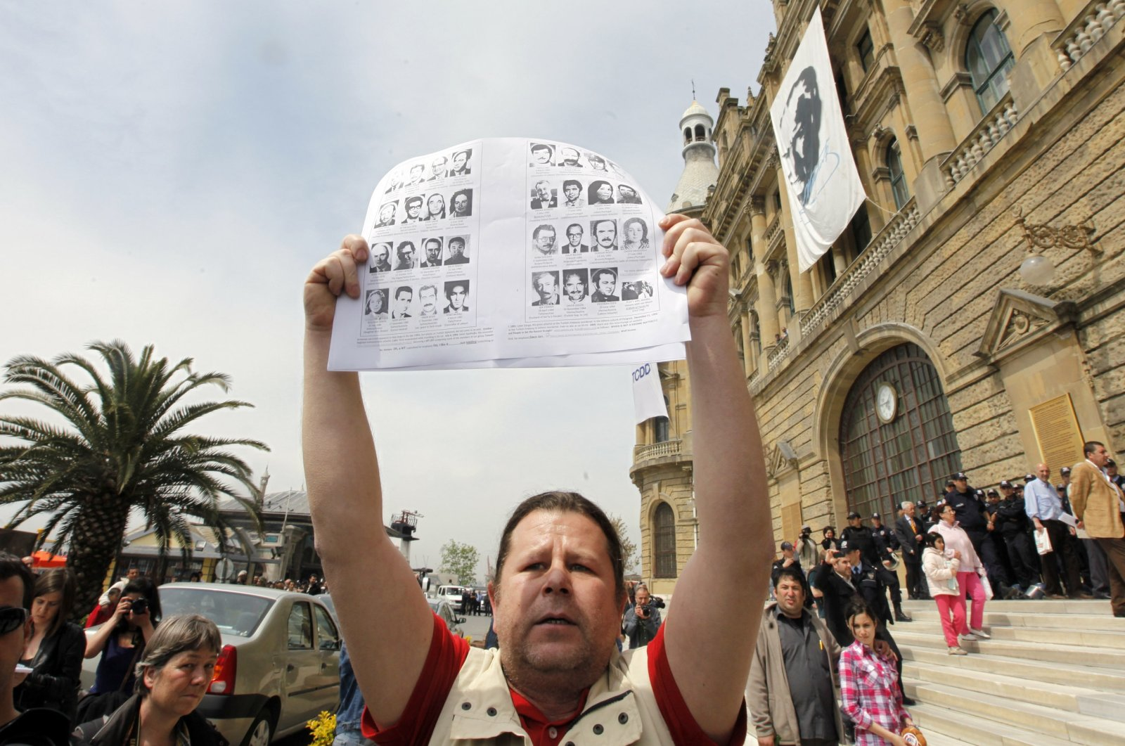 A Turkish man holds pictures of Turkish officials, including ambassadors and consuls, who were killed by a terrorist belonging to the now-defunct Armenian Secret Army for the Liberation of Armenia (ASALA), in response to a demonstration to commemorate the 1915 events in the Ottoman Empire, in front of the historical Haydarpaşa station in Istanbul, Turkey, April 24, 2010. (Reuters Photo)